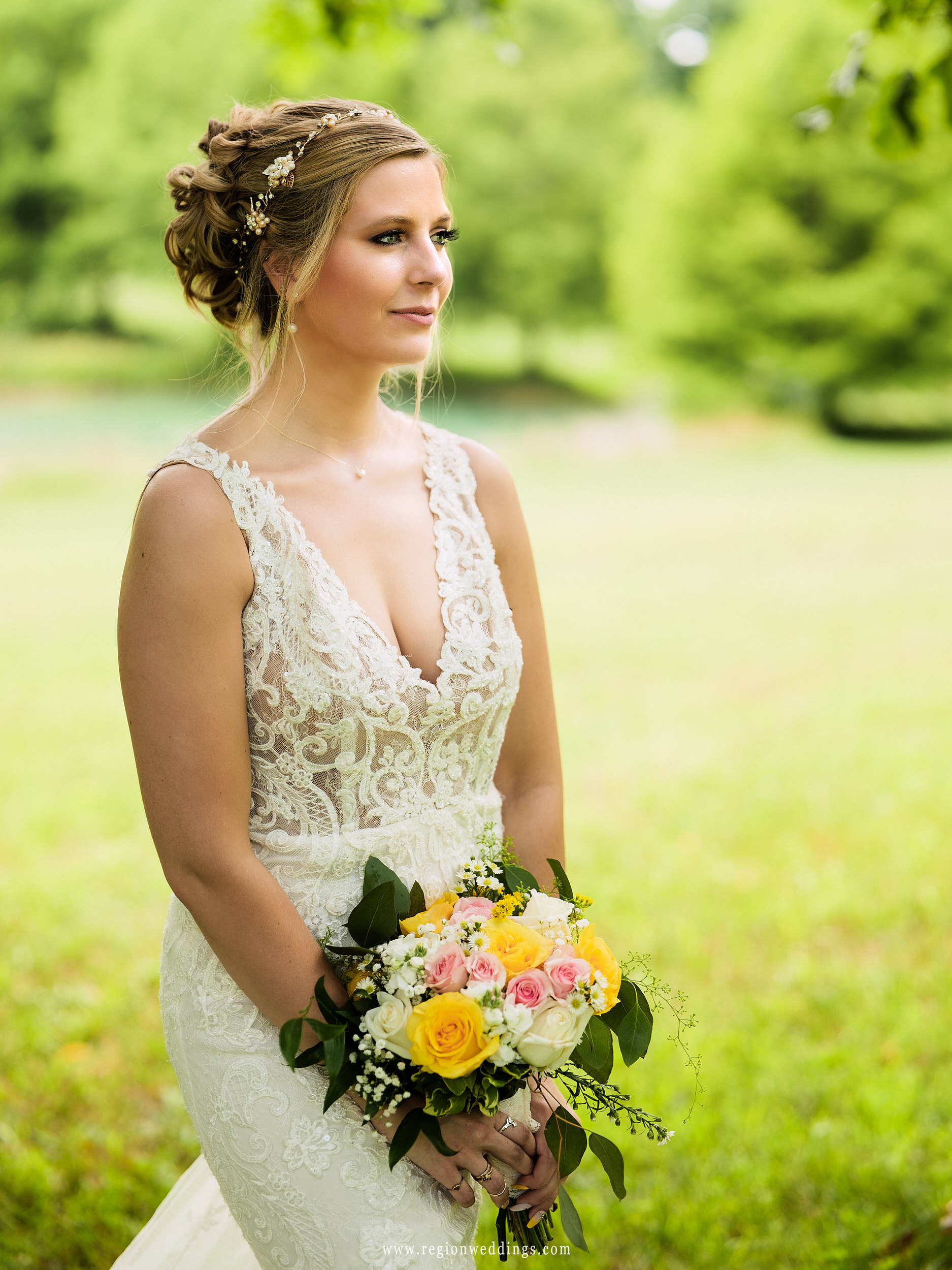 The bride looks across the beautiful green fields on her wedding day.