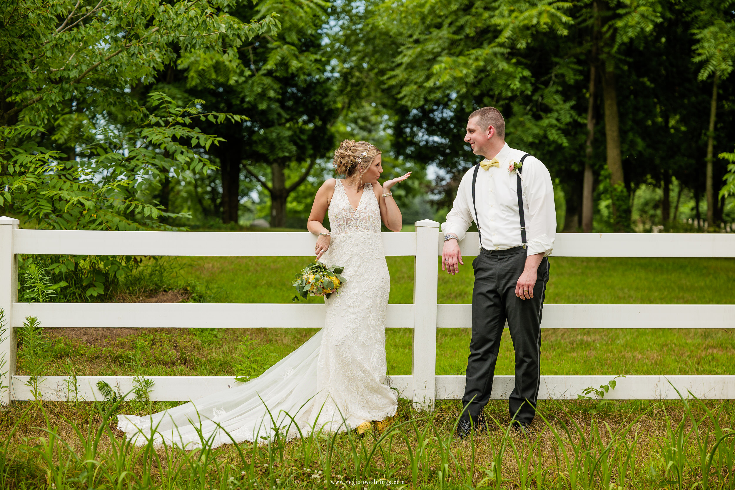 The bride blows kisses toward her new husband as they lean against a white picket fence.