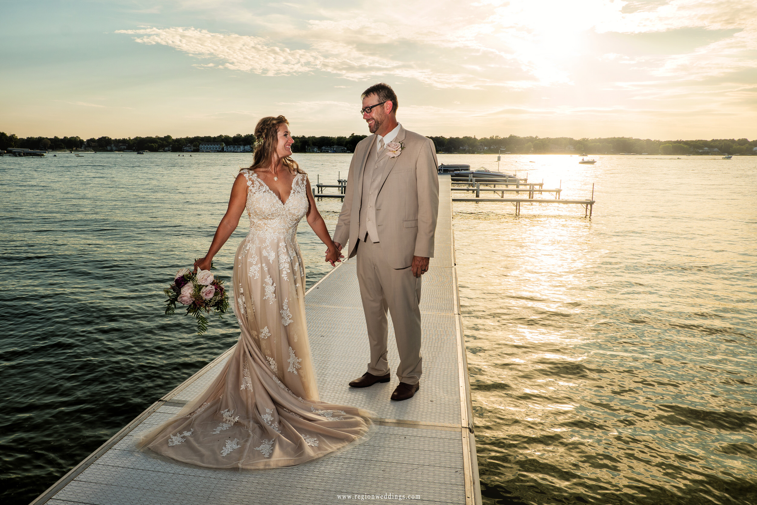 The bride twist toward her groom as the sun shines over the lake.