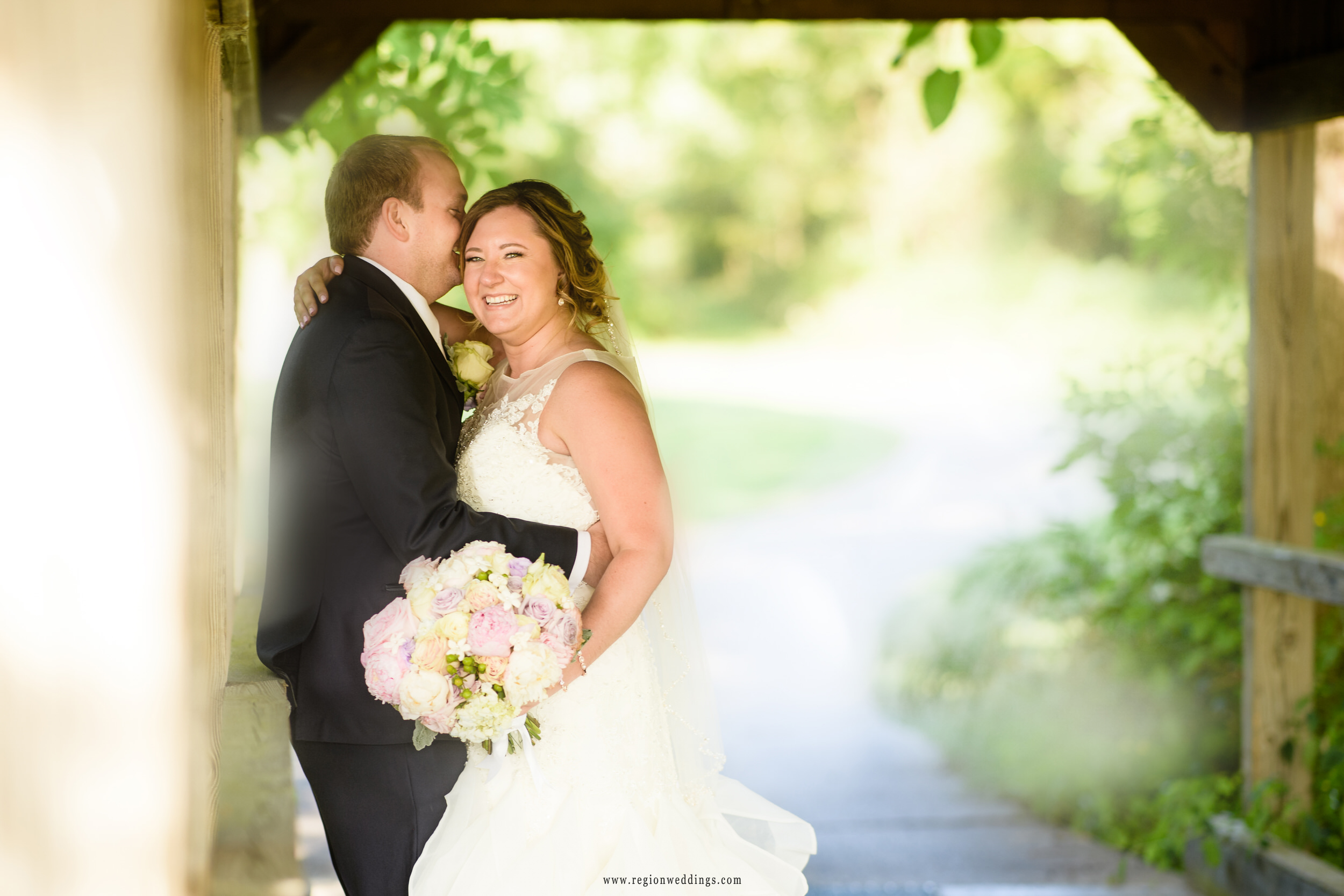 A candid moment between bride and groom underneath the covered bridge at Sand Creek golf course.