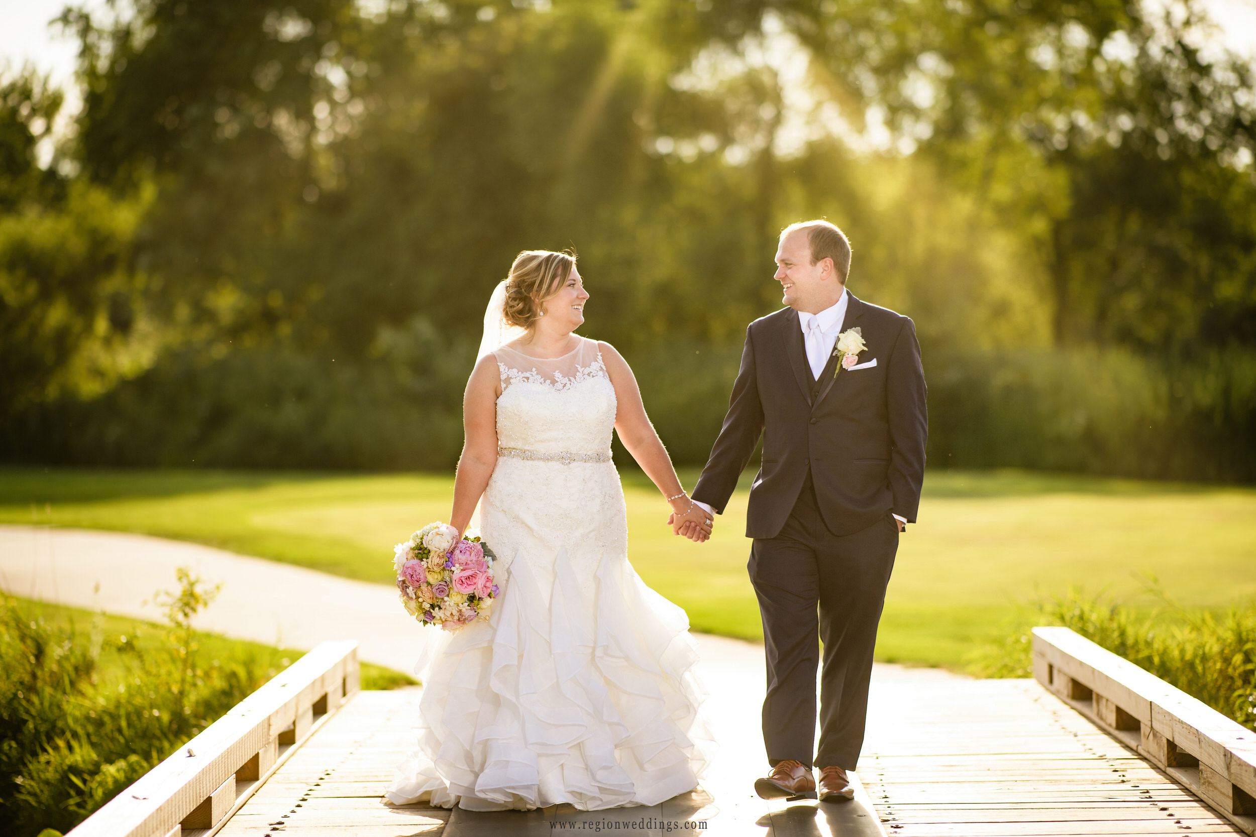 Bride and groom walking in the sunshine over the bridge at Sand Creek Country Club.