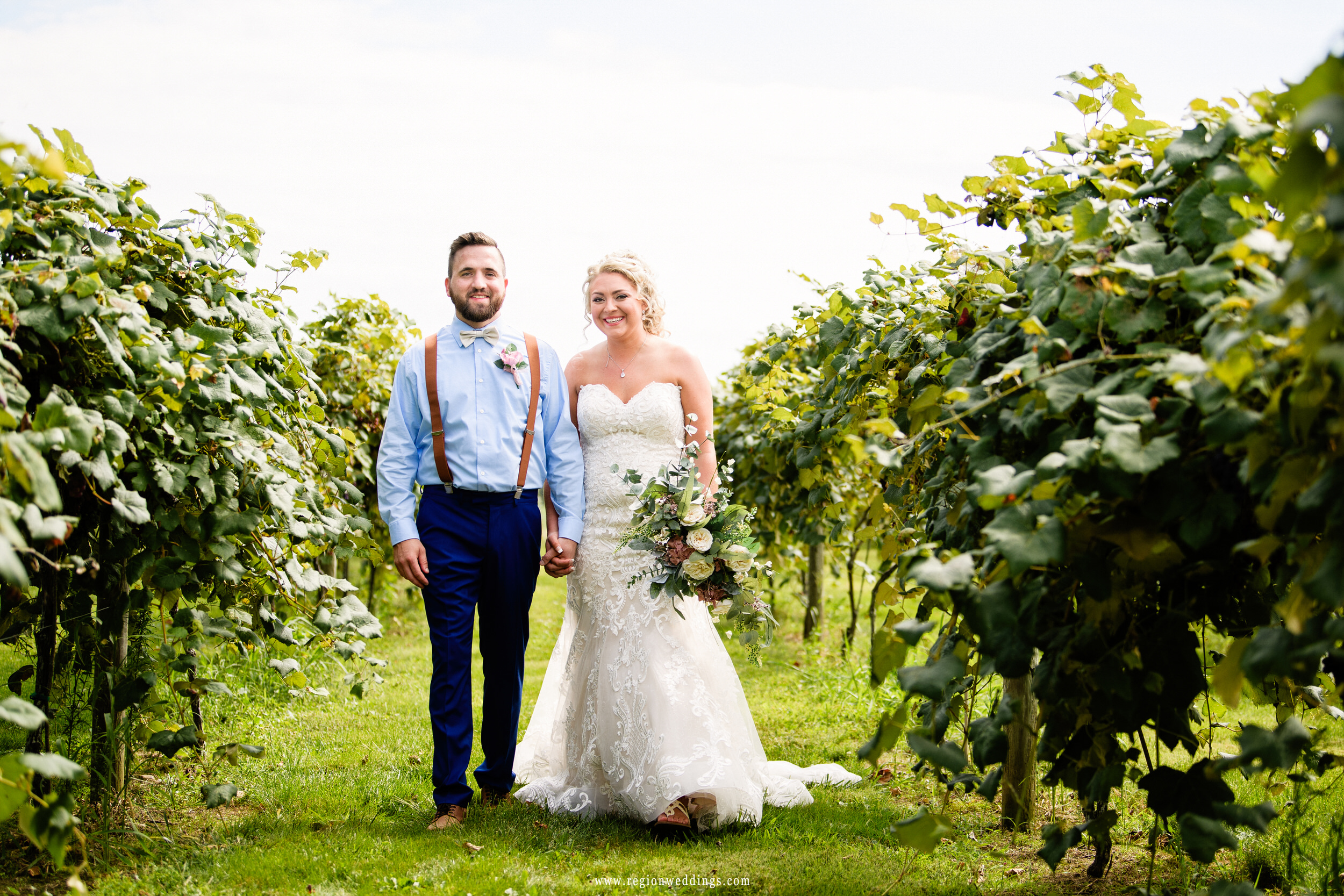The bride and groom take a stroll through the grape orchards.