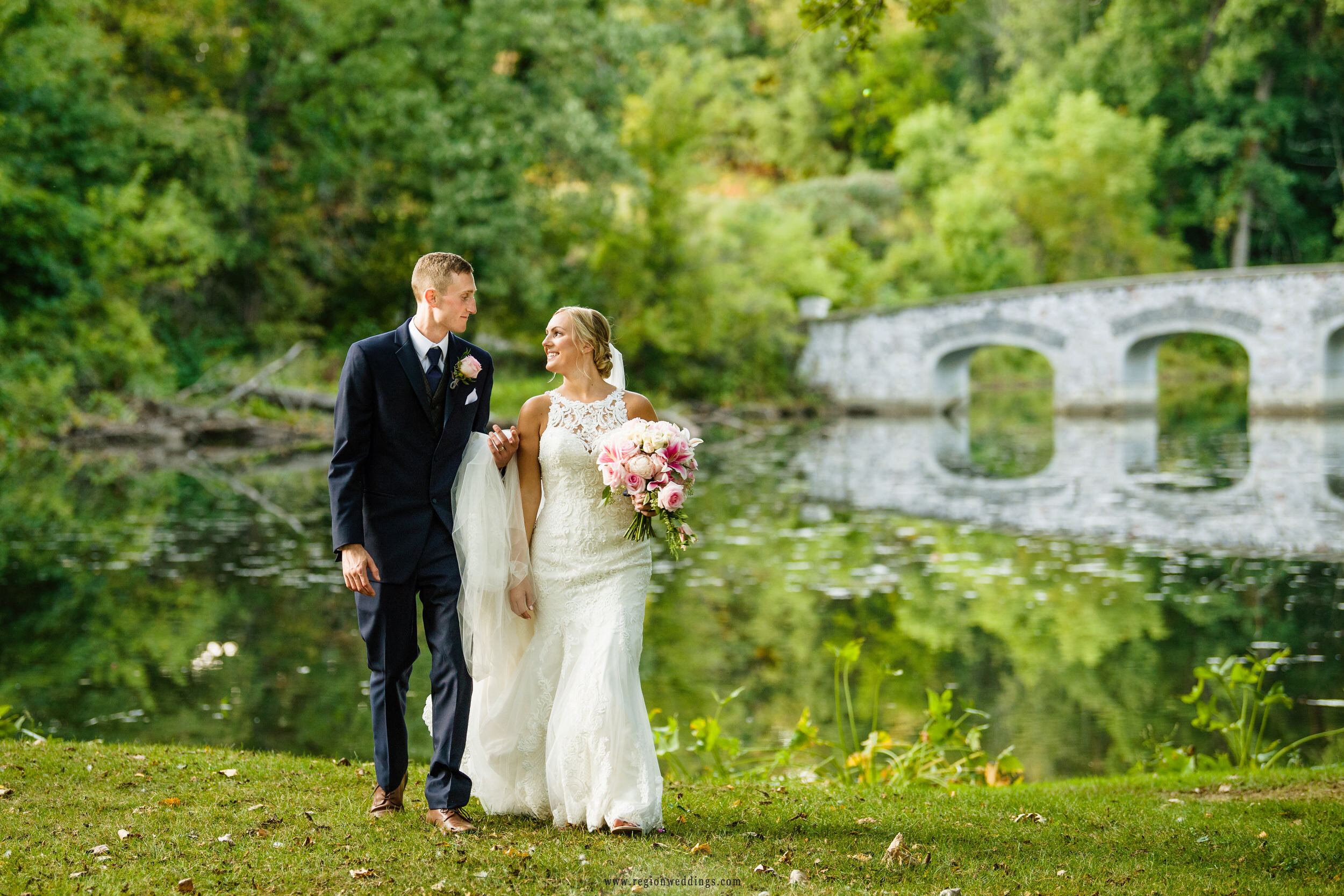 A bridge reflects across the water as the groom assist his bride across the field.