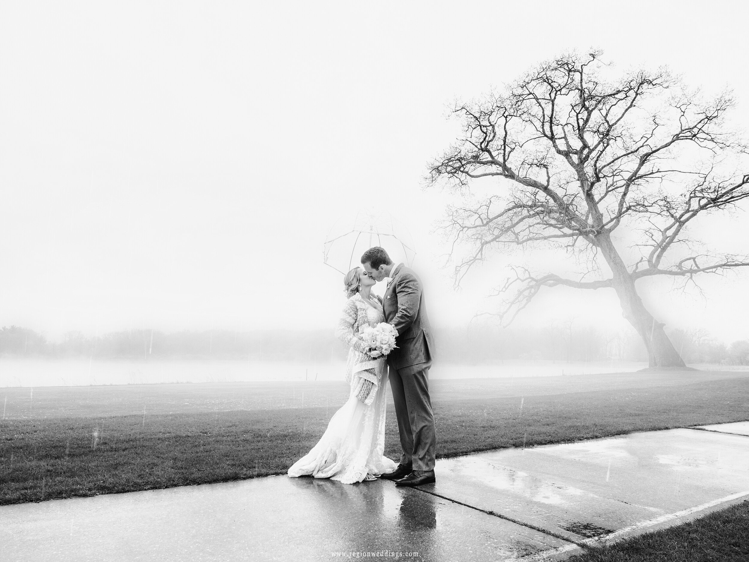 Wind and rain descend upon the bride and groom during their wedding photos.
