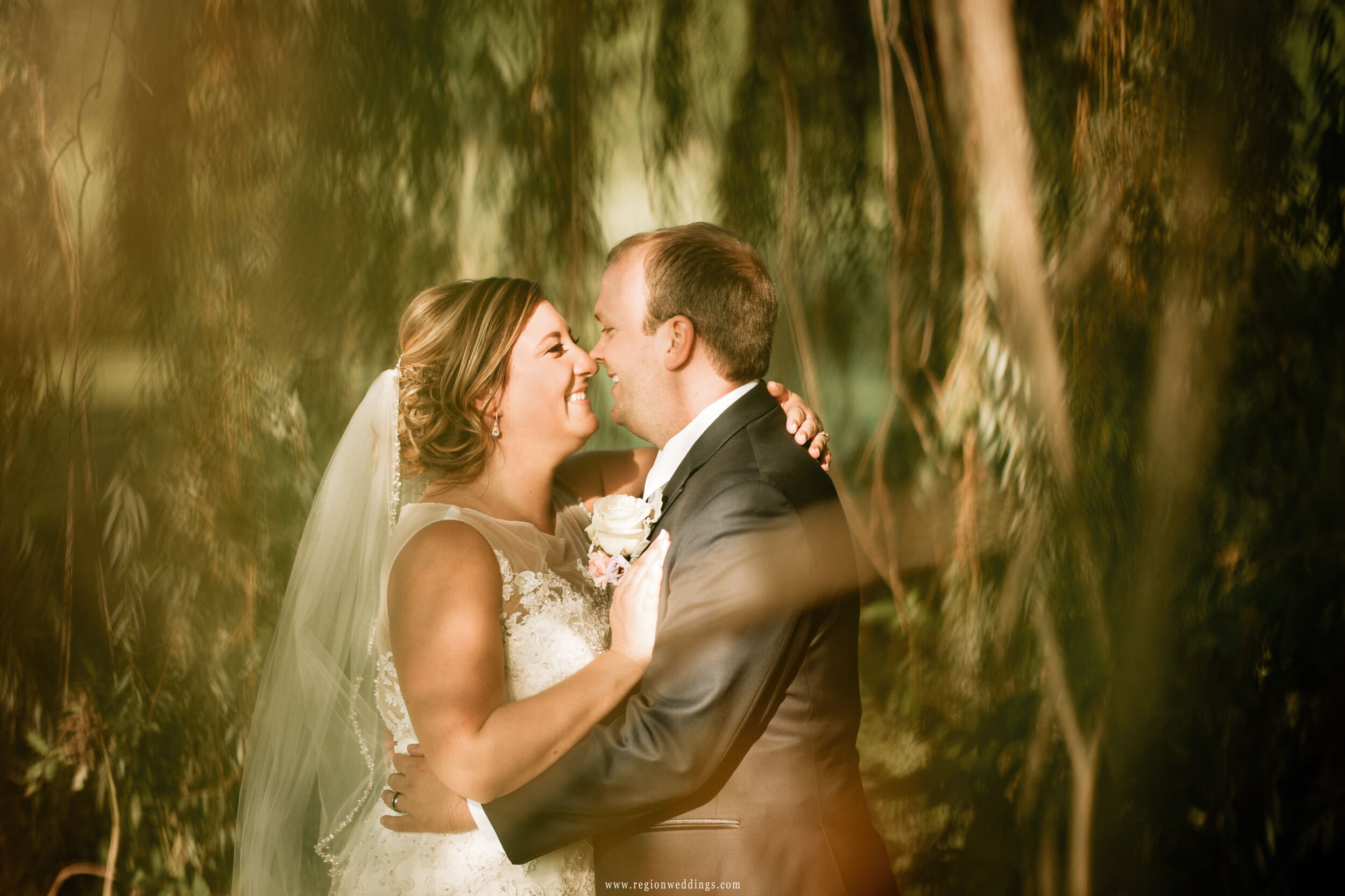 A fun moment between bride and groom underneath a weeping willow tree.