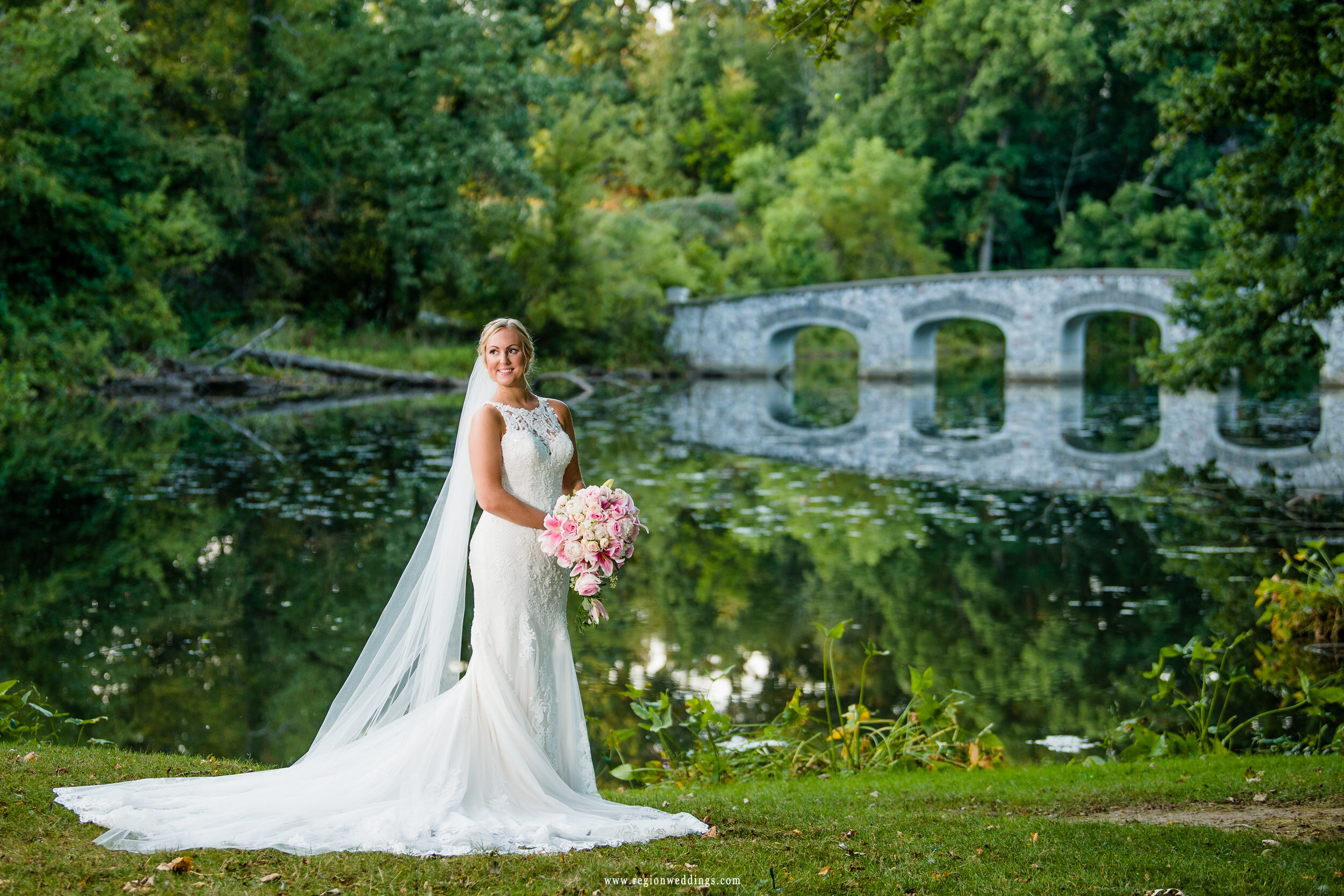 The bride standing near the river as the bridge reflects off the water.