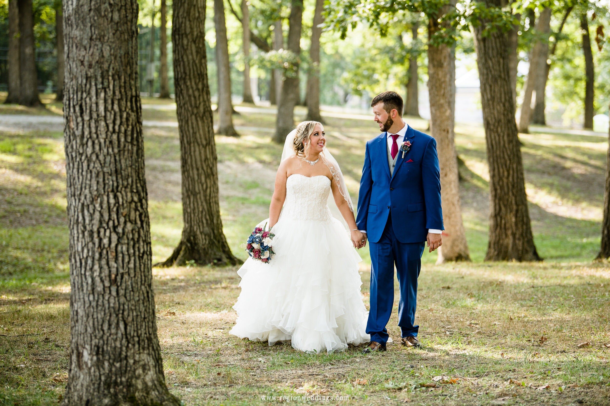 Bride and groom take a walk in the woods at Lake County Fairgrounds.