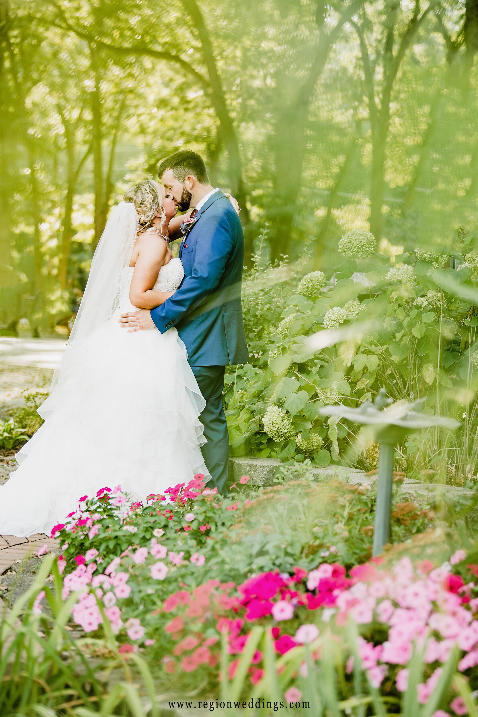 A flower garden surrounds the bride and groom in this romantic wedding photo.