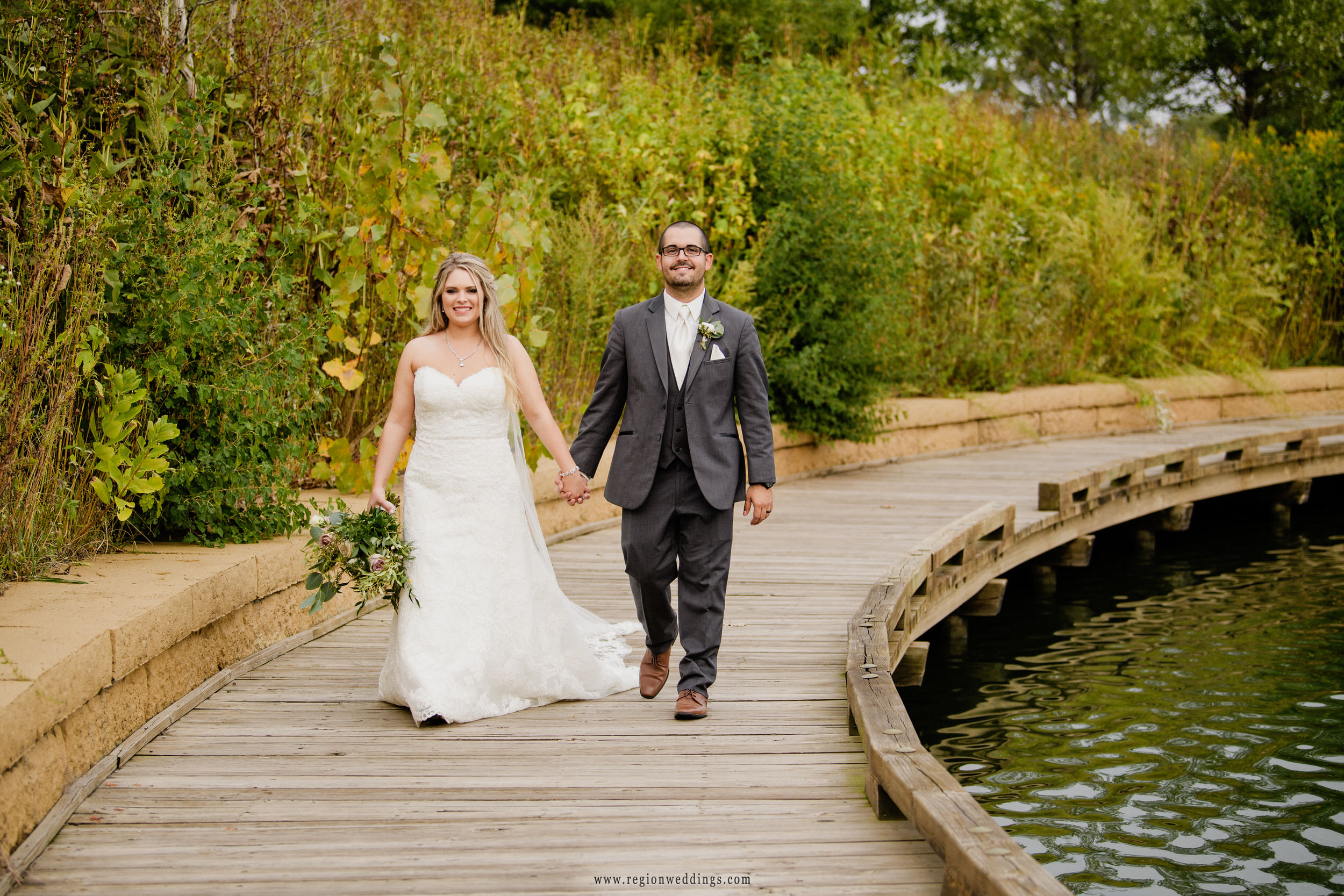 Bride and groom take a walk along the lake at Centennial Park in Munster, Indiana.