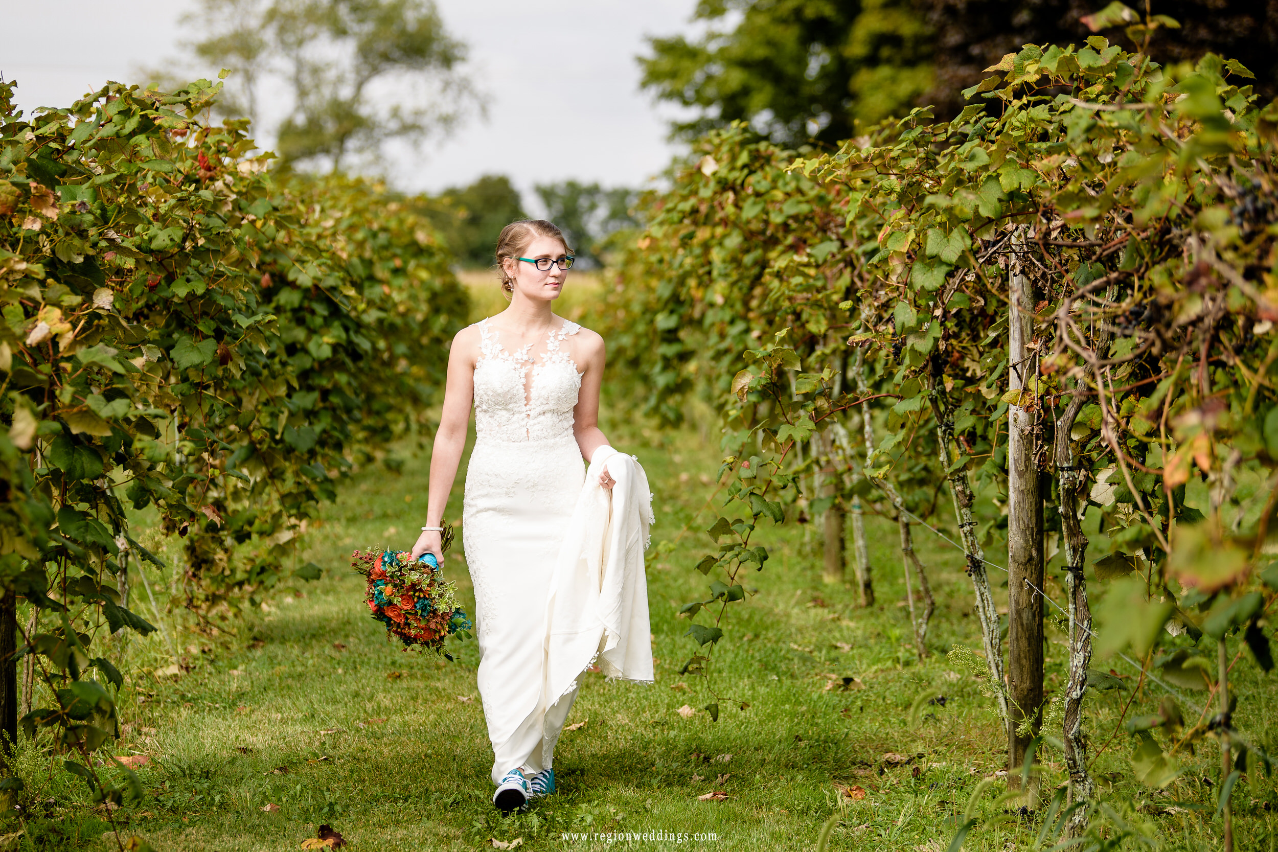 A boho styled bride walks along the grape orchards in her Converse All Star sneakers.