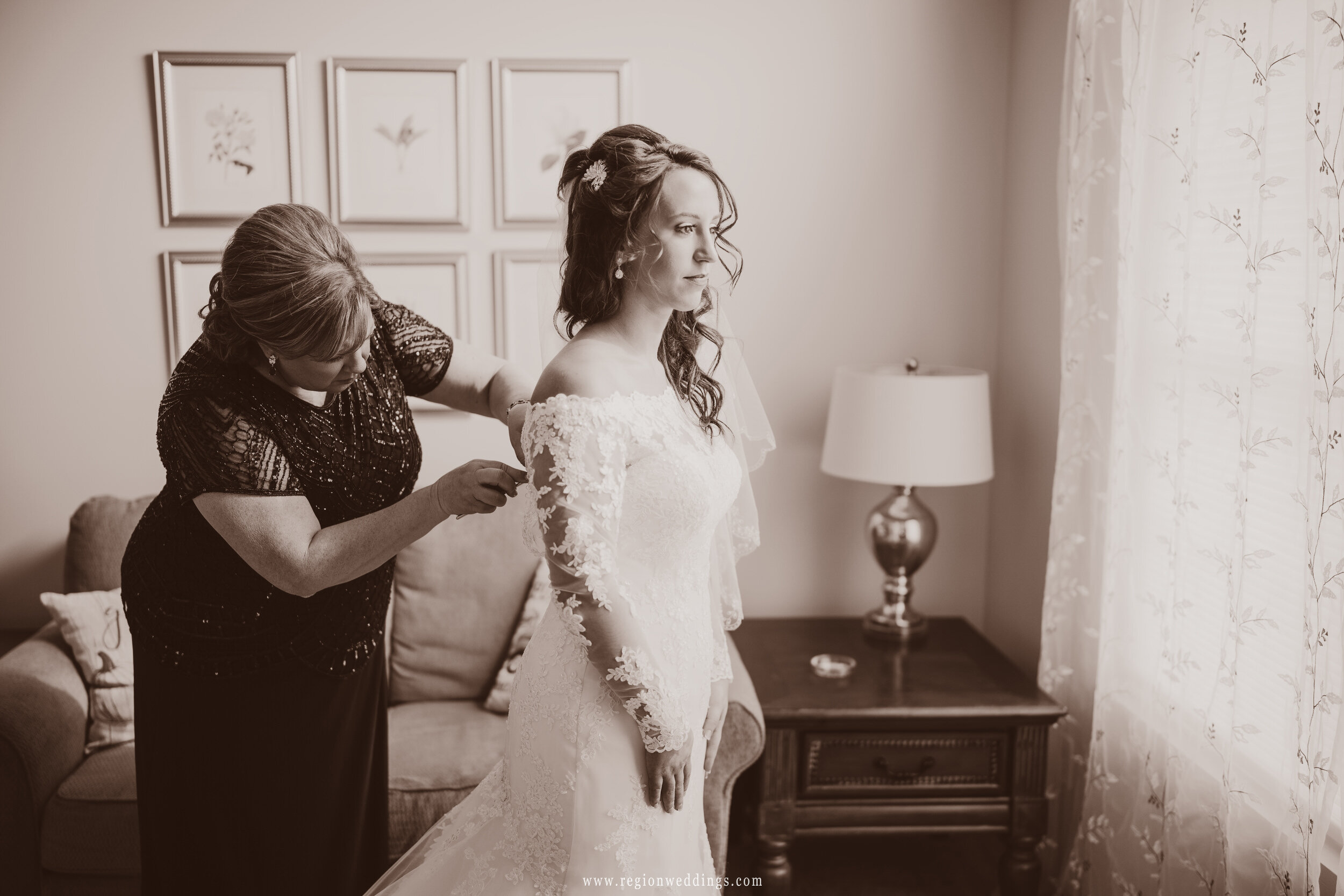 Mom helps her daughter into her dress on wedding day.