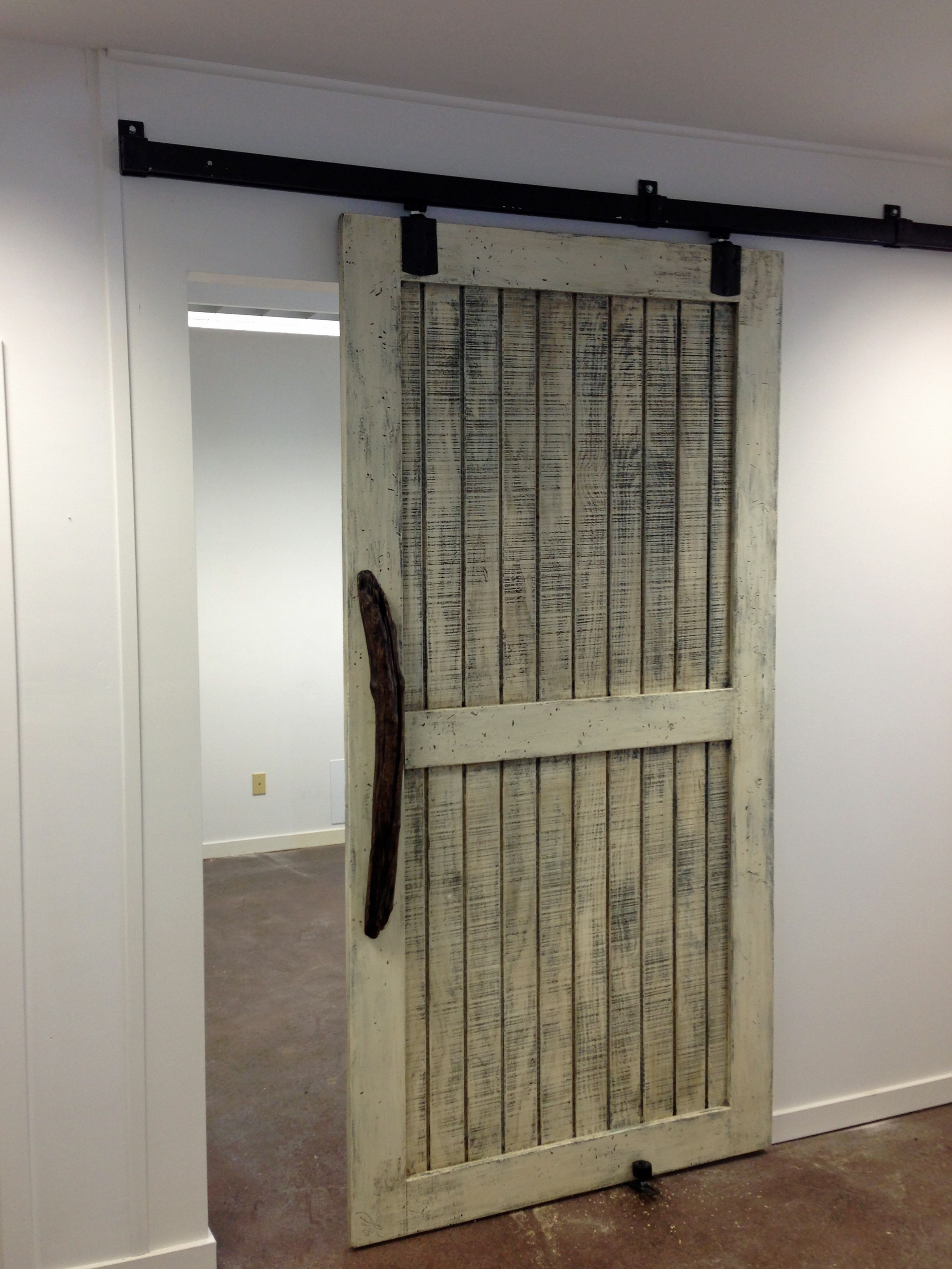 "The finished door. Mounted on a sliding barn door track, the door allows easy access with an 84"" high by 42"" wide opening."