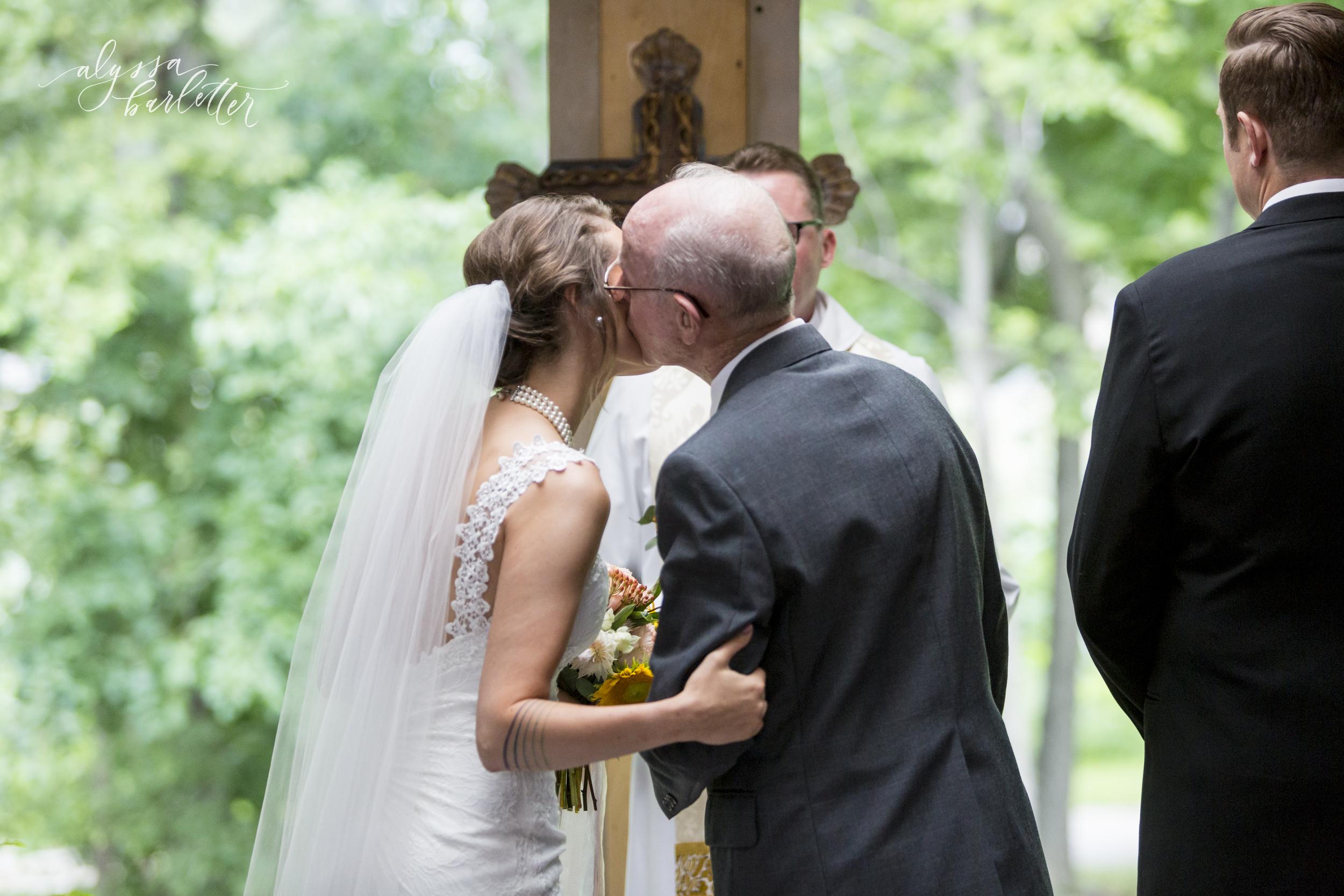 kansas city wedding budget mahaffie bride giving kiss ceremony
