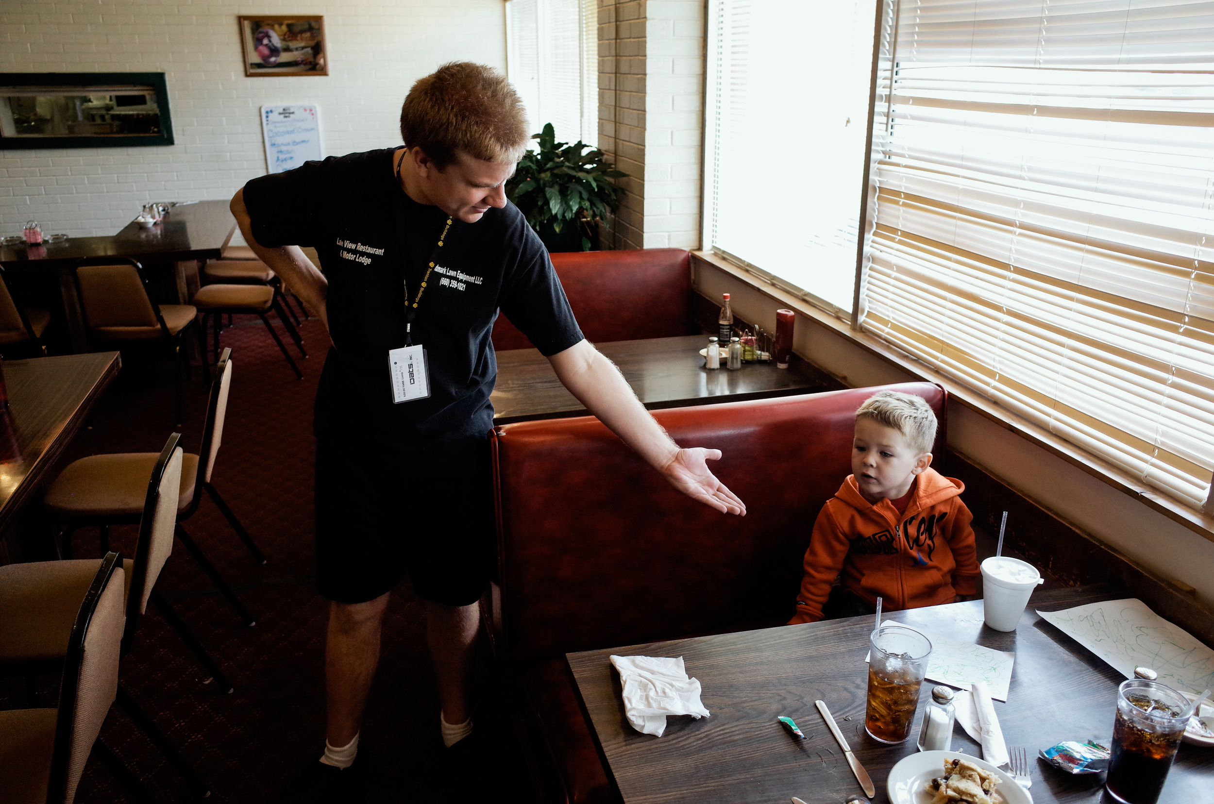 Trenton, Missouri. 2013.  One day a week Dalton works at the Lakeview Motor Lodge and Restaurant rolling silverware and wiping chairs. He always finds time to share a moment with customers.