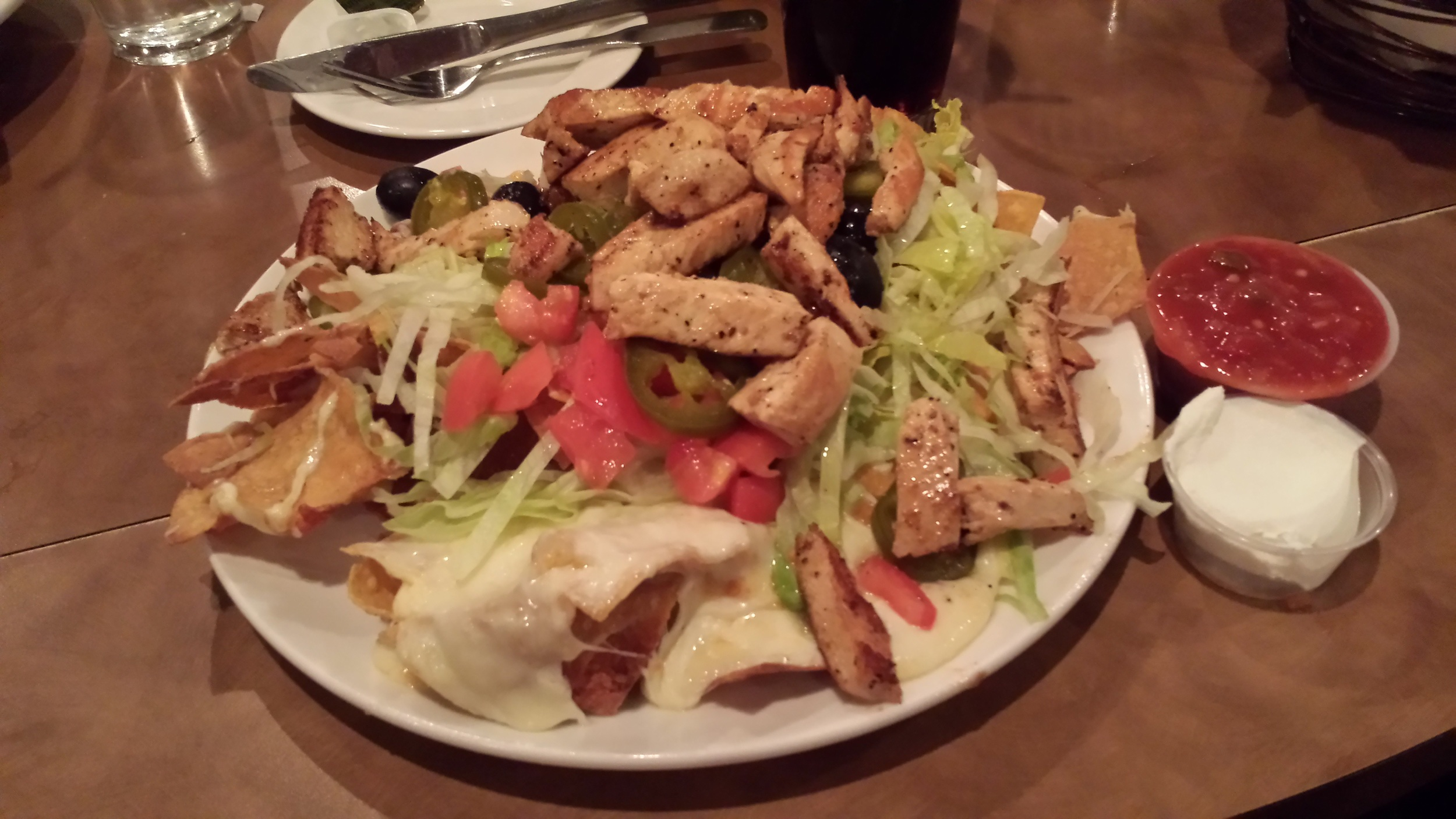 Tortilla Chips, Cheese, Chicken, Tomatoes, Lettuce, Jalapenos, Black Olives.
