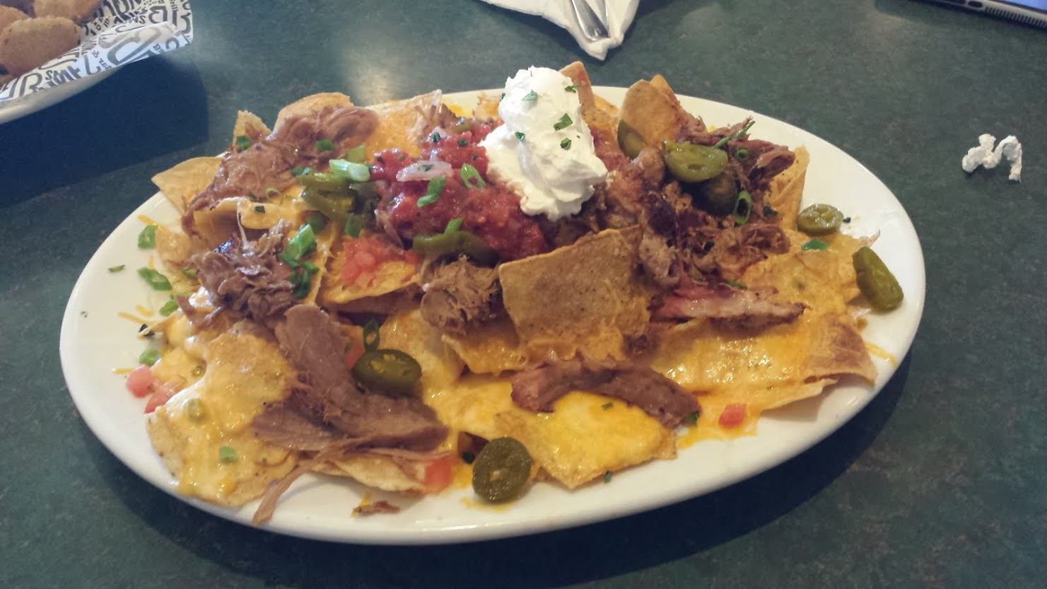 Tortilla Chips, Homemade Queso, Cheddar Jack Cheese, Tomatoes, Red Onions, Shredded Lettuce, Sour Cream, Homemade Fire-Roasted Salsa, Sliced Jalapeños, Pulled Pork.