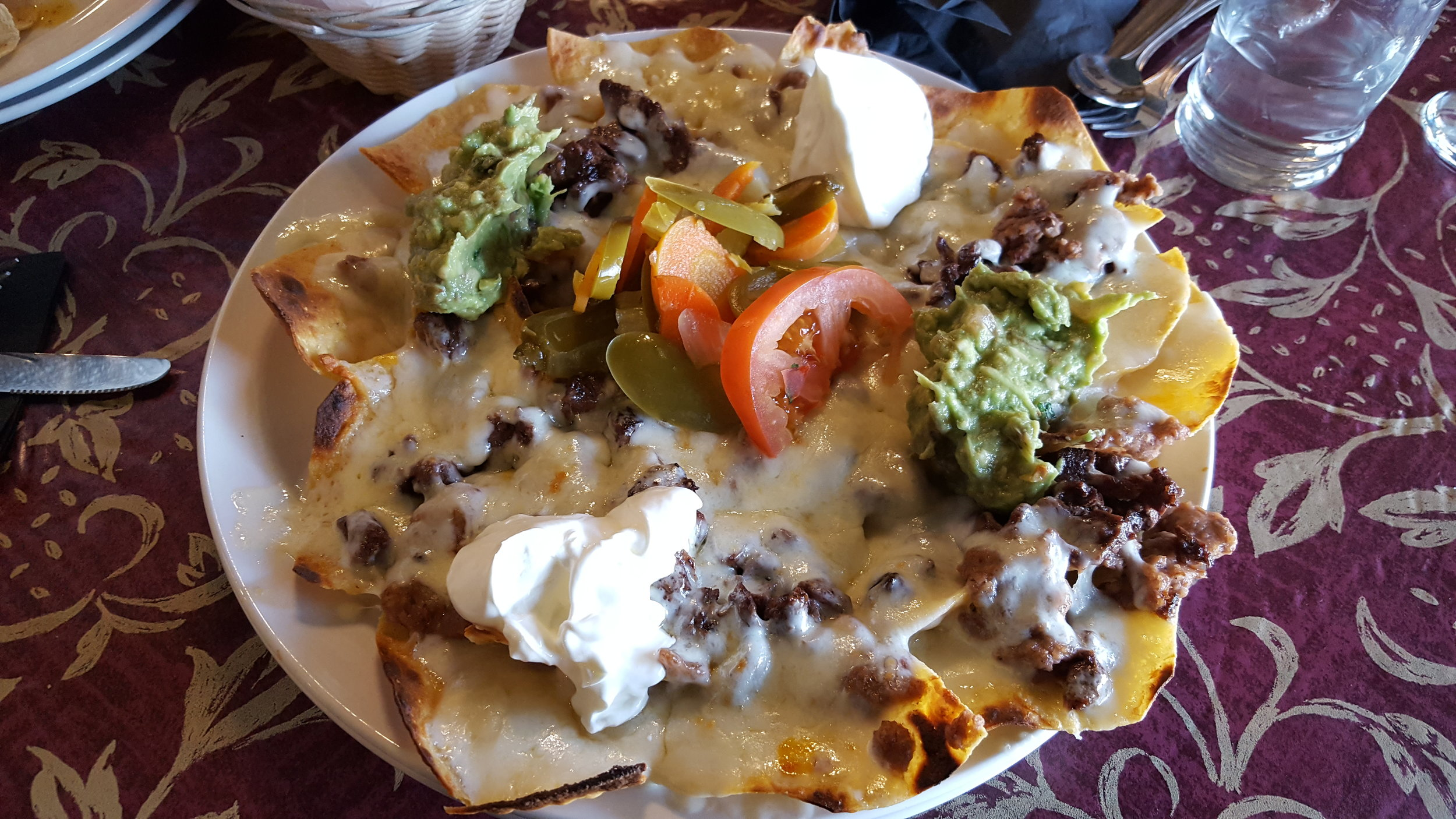 Fresh Tortilla Chips, Beans, Melted Cheese, Guacamole, Sour Cream, Jalapeno Peppers, Tomatoes, Steak