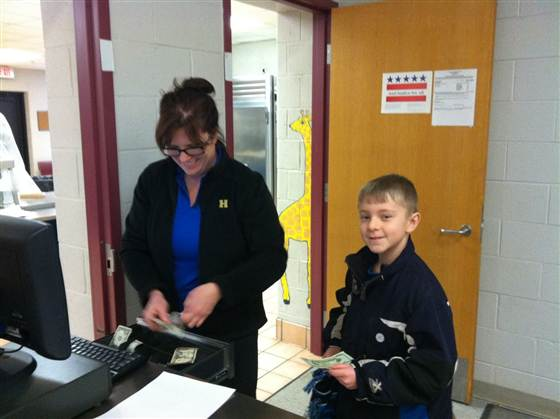 Cayden Taipalus hands money to a food service worker at Challenger Elementary.
