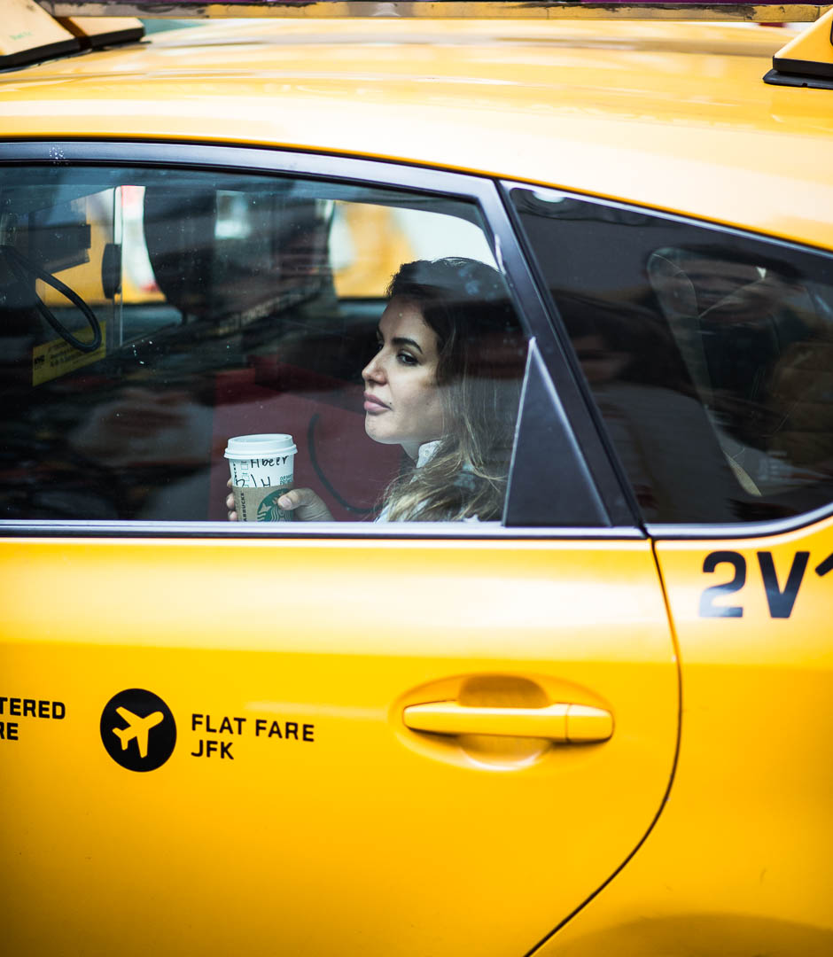 Woman in Cab  Photos by Charles D. McCain  Times Square is one of the most eclectic areas in the world, filled with energy and attitude. It's rare you can find a small minute to enjoy a simple cup of coffee. I saw this woman in a Taxi as it passed through the Square, and I wondered what she was thinking while sipping her coffee and enjoying a cab ride.