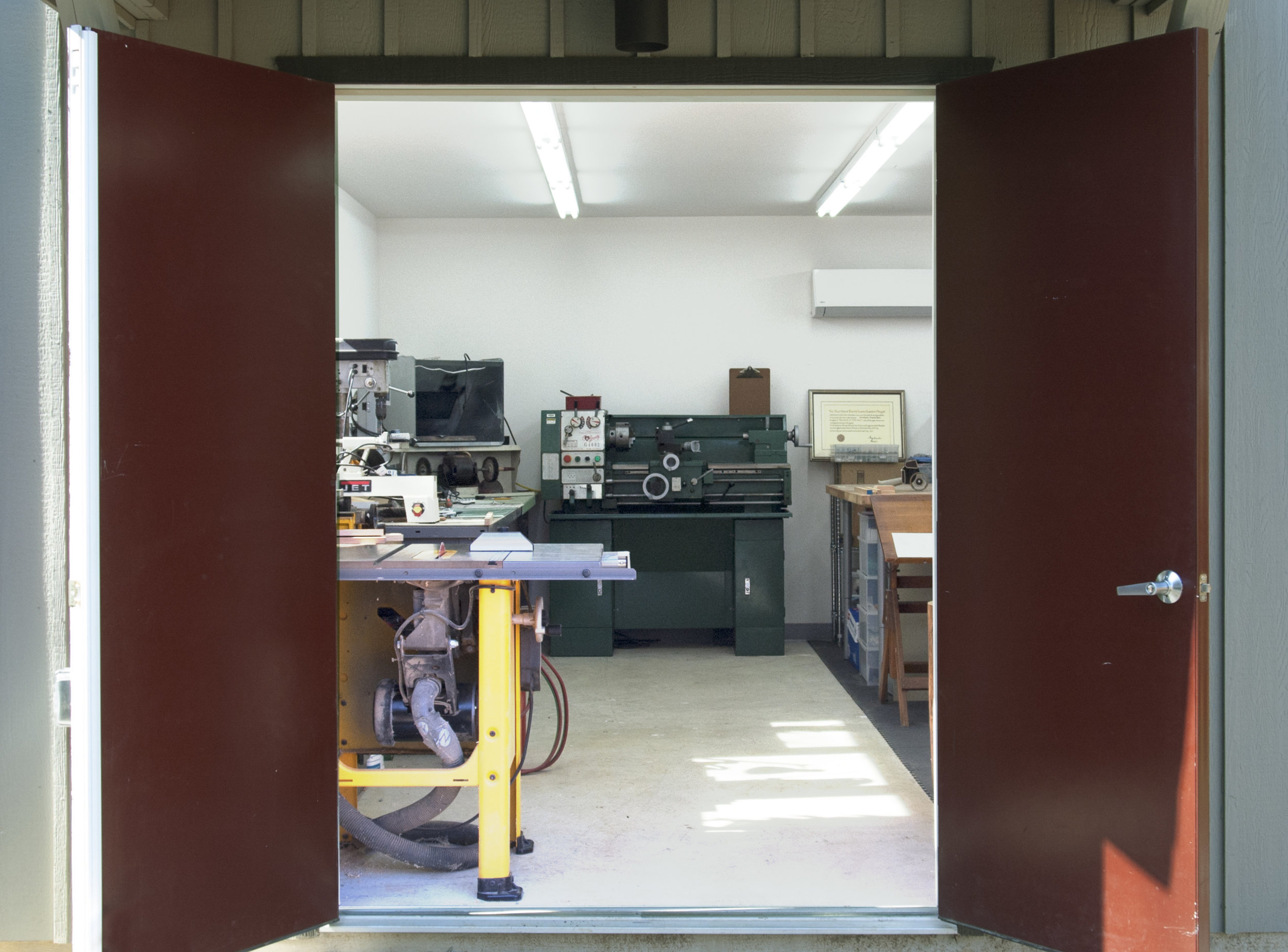 When Chris needs to cut a long piece of wood on the table saw, we move the table saw over and open the doors. You can see our new-­‐to-­‐us green metal lathe against the back wall. Andy's studio is off to the right.