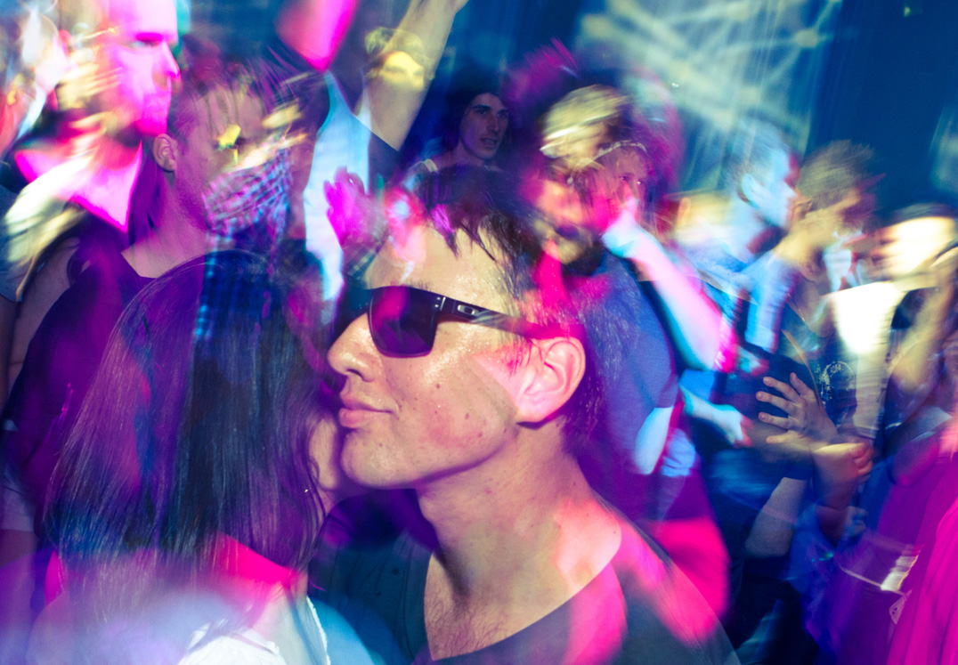 Two young people dance during an EDM concert.