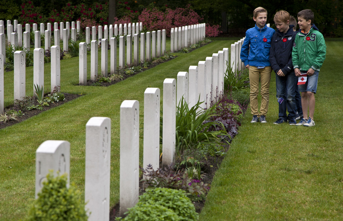Children quickly locate the grave of Canadian Chaplin Reverend T.E. Mooney, killed 14th Sep. 1944.