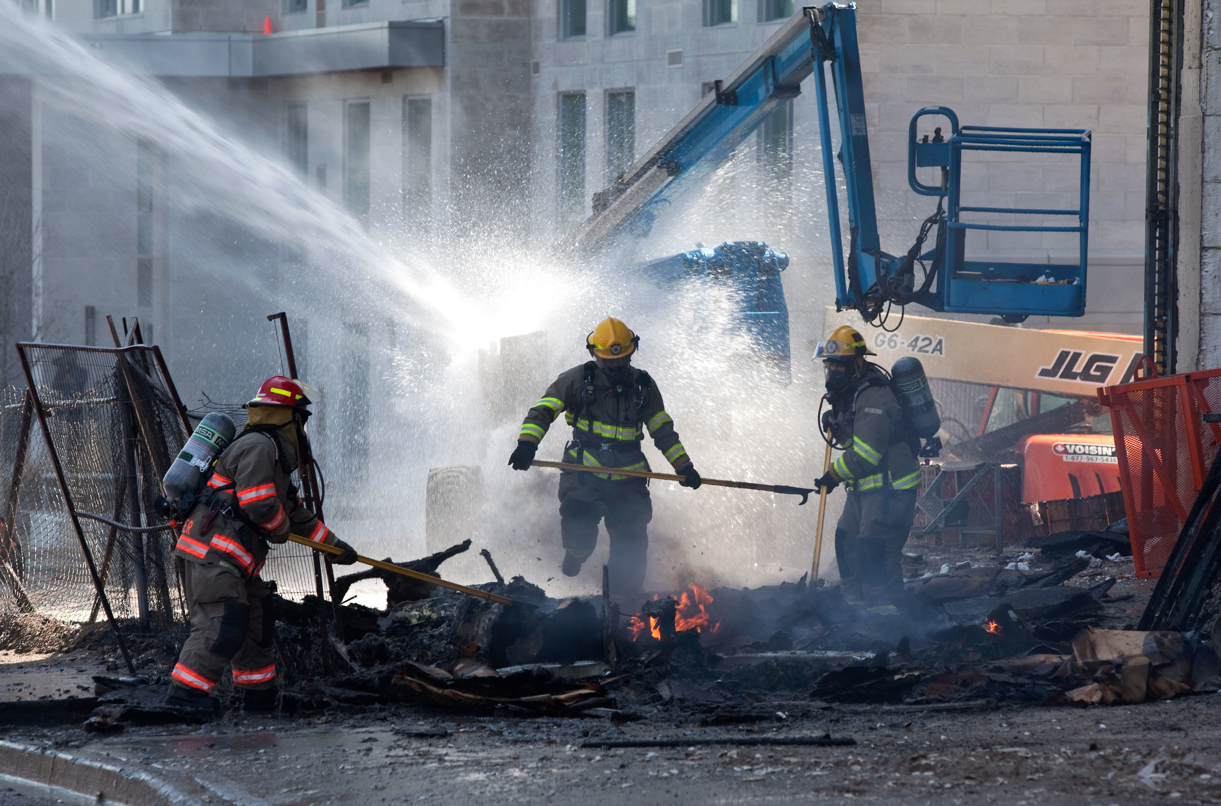 Firefighters finish off a blaze started when a lift overheated andexploded at a construction site in Waterloo.