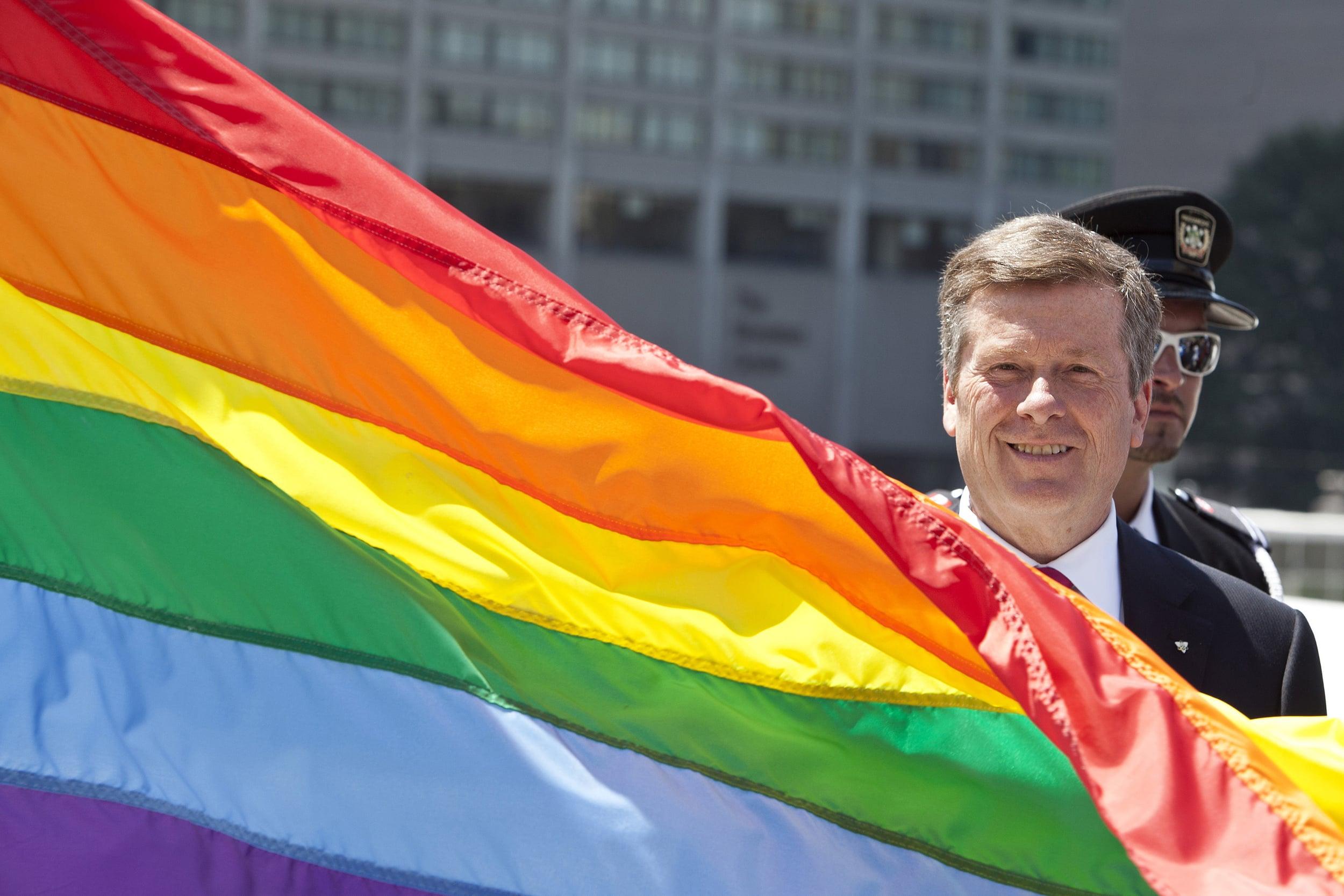 Toronto Mayor John Tory raises the Pride flag at Toronto city hall.