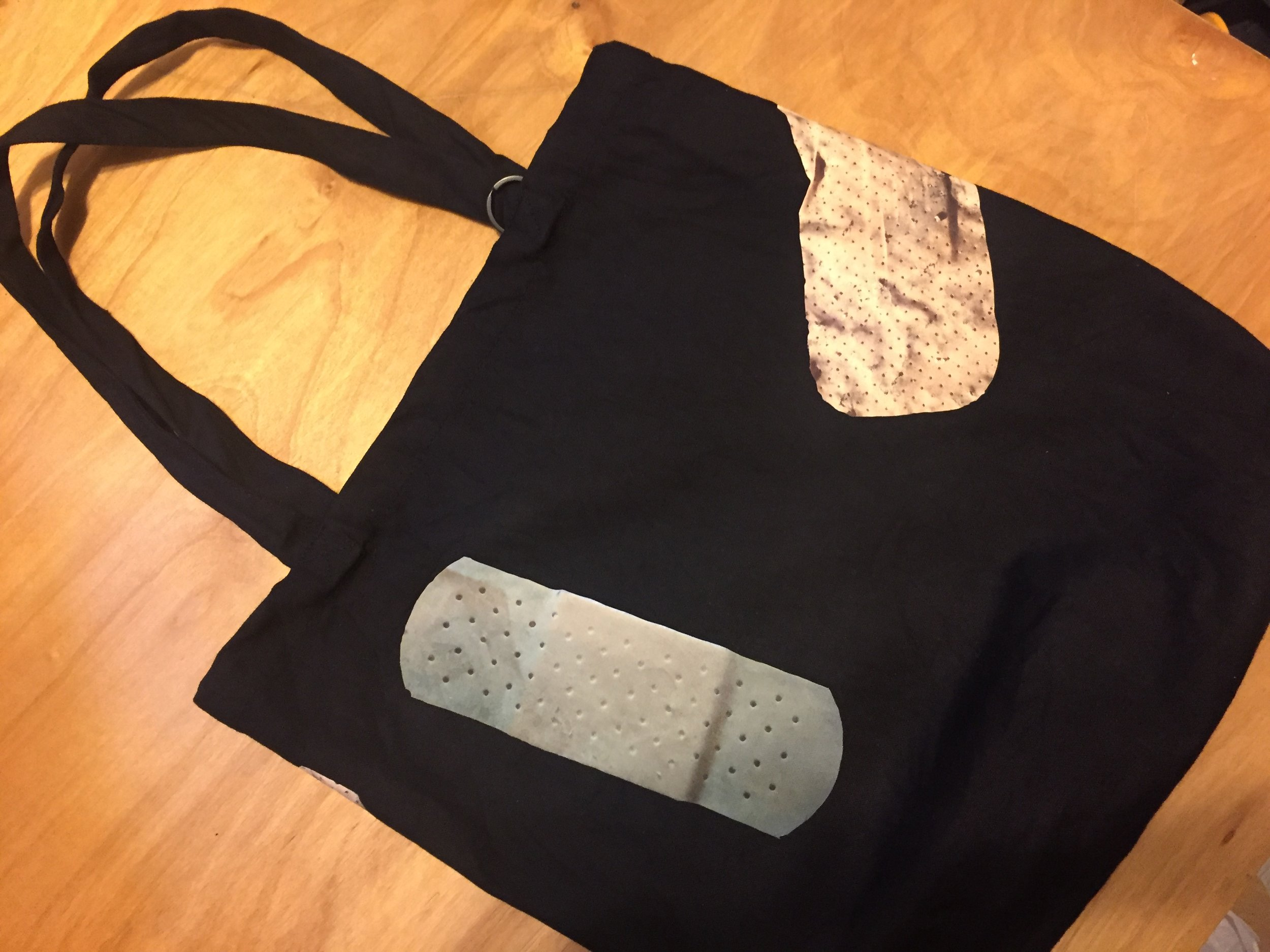 "Bandage Tote Bag. Iron-oned, Pre-washed, Preshrunk. 10oz 100% Cotton canvas. 15"" x 15"" x 4"". Each Bandage was documented on the street using cellphone camera by Niizeki Hiromi."