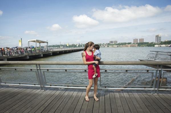Caitlin com uma das três crianças de quem cuida. Ela diz que frequentemente é confudida com a mãe deles.