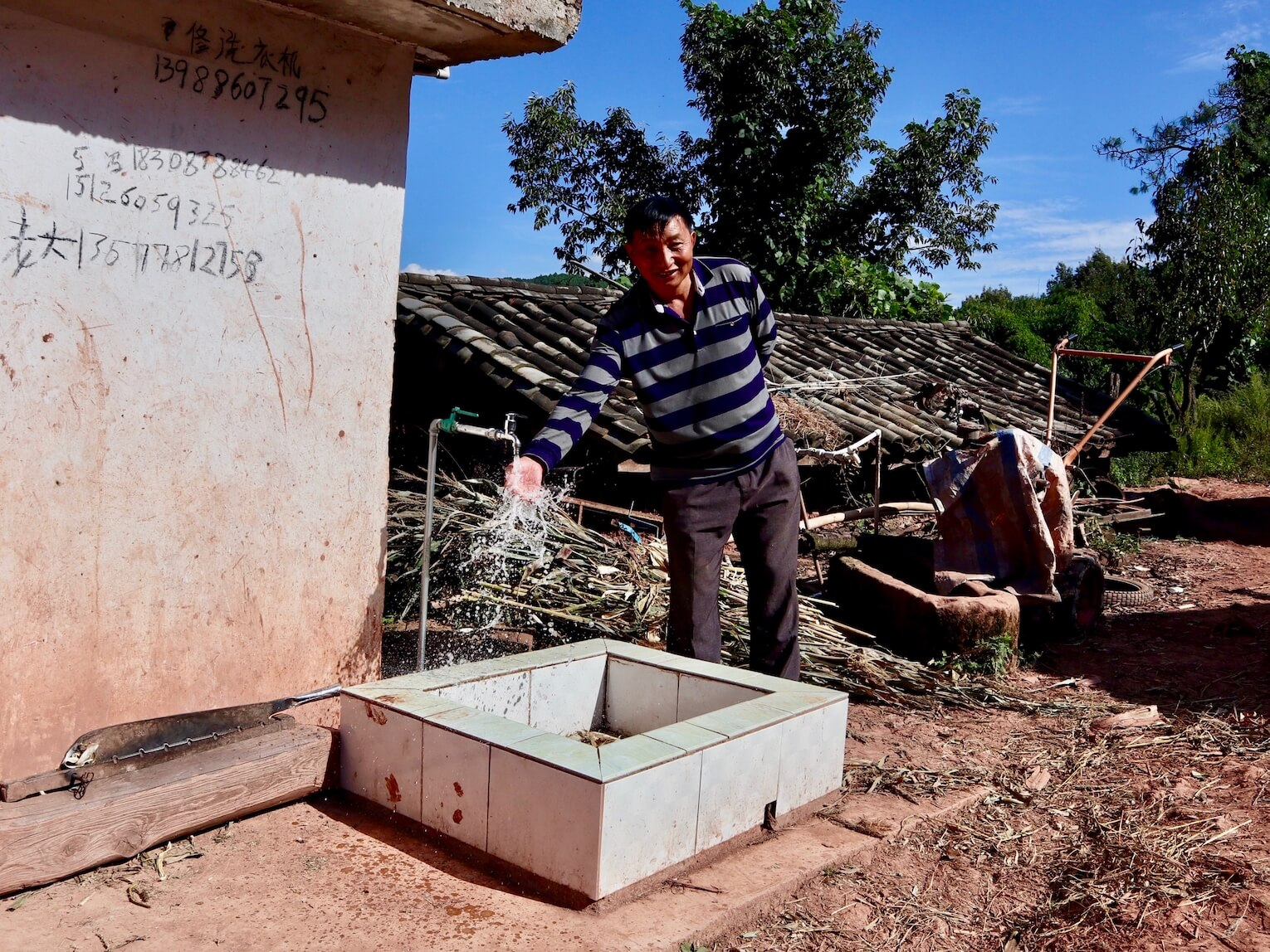 A happy customer at a new drinking water project site in rural Yunnan