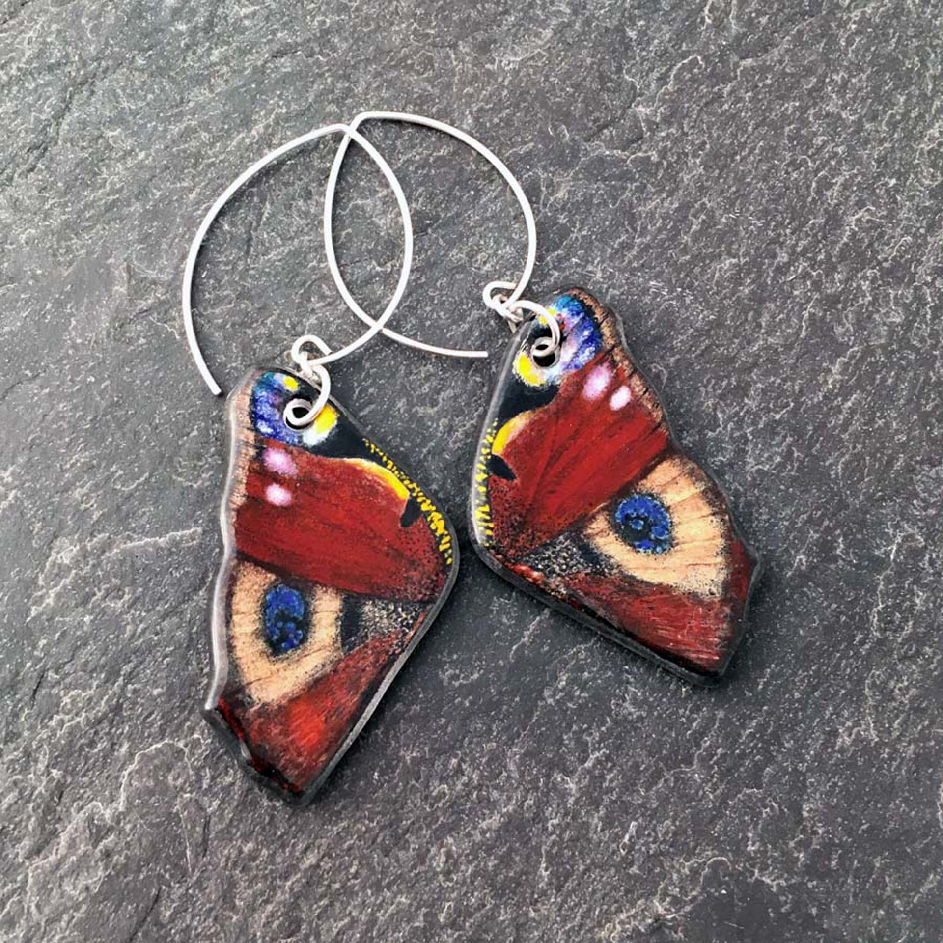 """3. Peacock Butterfly Earrings, kiln formed art glass, 1"""" x 2.5"""" x .25"""", Earrings, image painted with glass enamels, clear art glass, Argentium sterling silver ear wires, $175.00."""