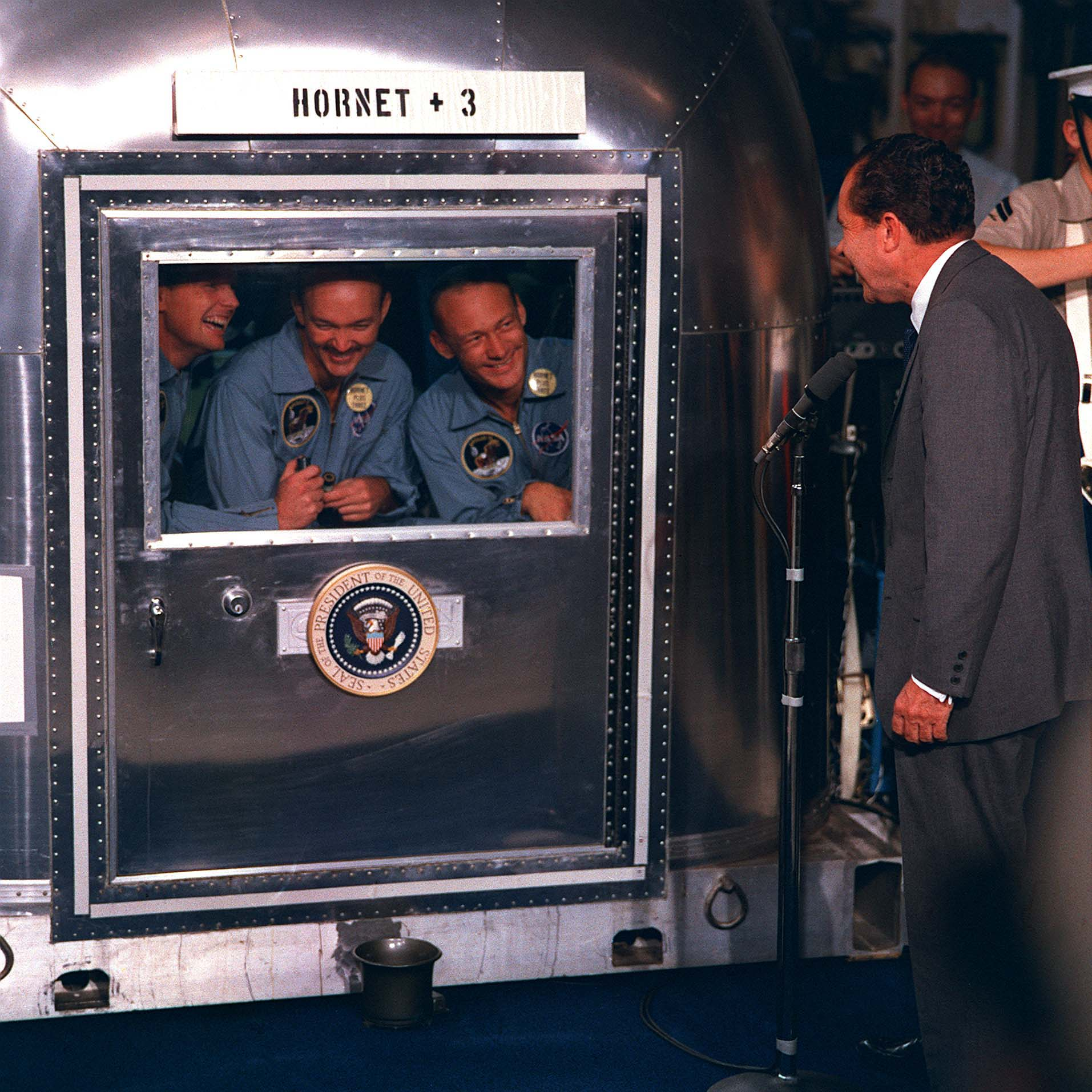 President Richard Nixon greets Apollo 11 astronauts Neil Armstrong, Michael Collins, and Buzz Aldrin during their quarantine, July 24, 1969,  via NASA .