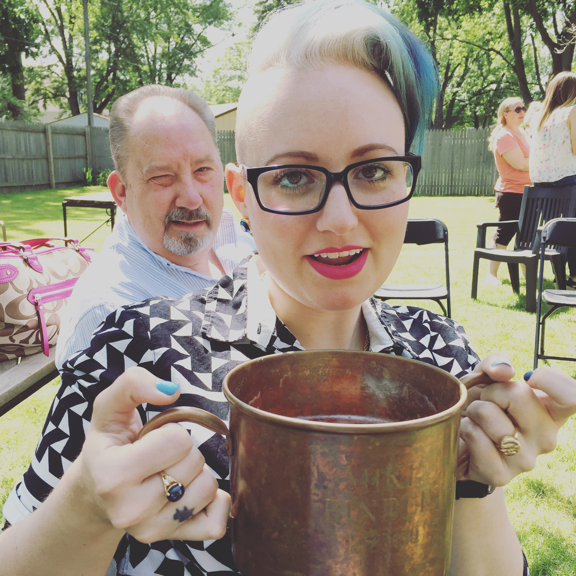 Speaking of death, that's me at the family function I mentioned last weekend. I am holding a copper bucket—full of beer—which I can not drink because I have a gluten allergy. So I sip it, because I believe it keeps my ancestors happy. It's a mitzvah, you know, to make yourself sick out of a self-imposed family obligation. A beautiful thing, no? I digress.This bucket comes out at EVERY family function, and everyone passes it around and drinks out of it. Everyone. [That's my Dad behind me. We have opposite hair patterns.]