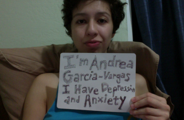 "Sign: ""I'm Andrea Garcia-Vargas and I have depression and anxiety.""    Image description: Young light-skinned Latina with short dark brown hair and deep blue tank top holding a sign."