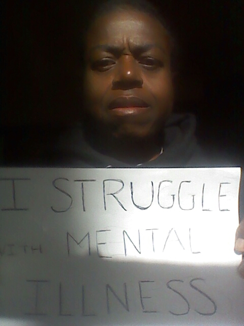 Sign: I struggle with mental illness.  Image description: Elder Black woman facing the screen with a short afro and a serious look on her face.