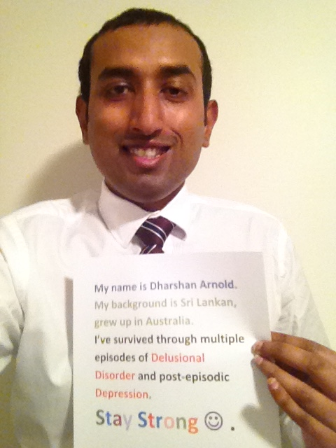 "Sign: ""My name is Dharshan Arnold. My background is Sri Lankan, grew up in Australia. I've survived through mulitple episodes of Delusional Disorder and Post-Episodic Depression. Stay Strong.""    Image description: 29 Year old Sri Lankan Australian man in a white business shirt and maroon tie with a bold blue stripe flanked by white stripes, looking into the camera, smiling widely with teeth visible and holding a multi-coloured sign gently on the tip of his index and middle fingers on his left hand."