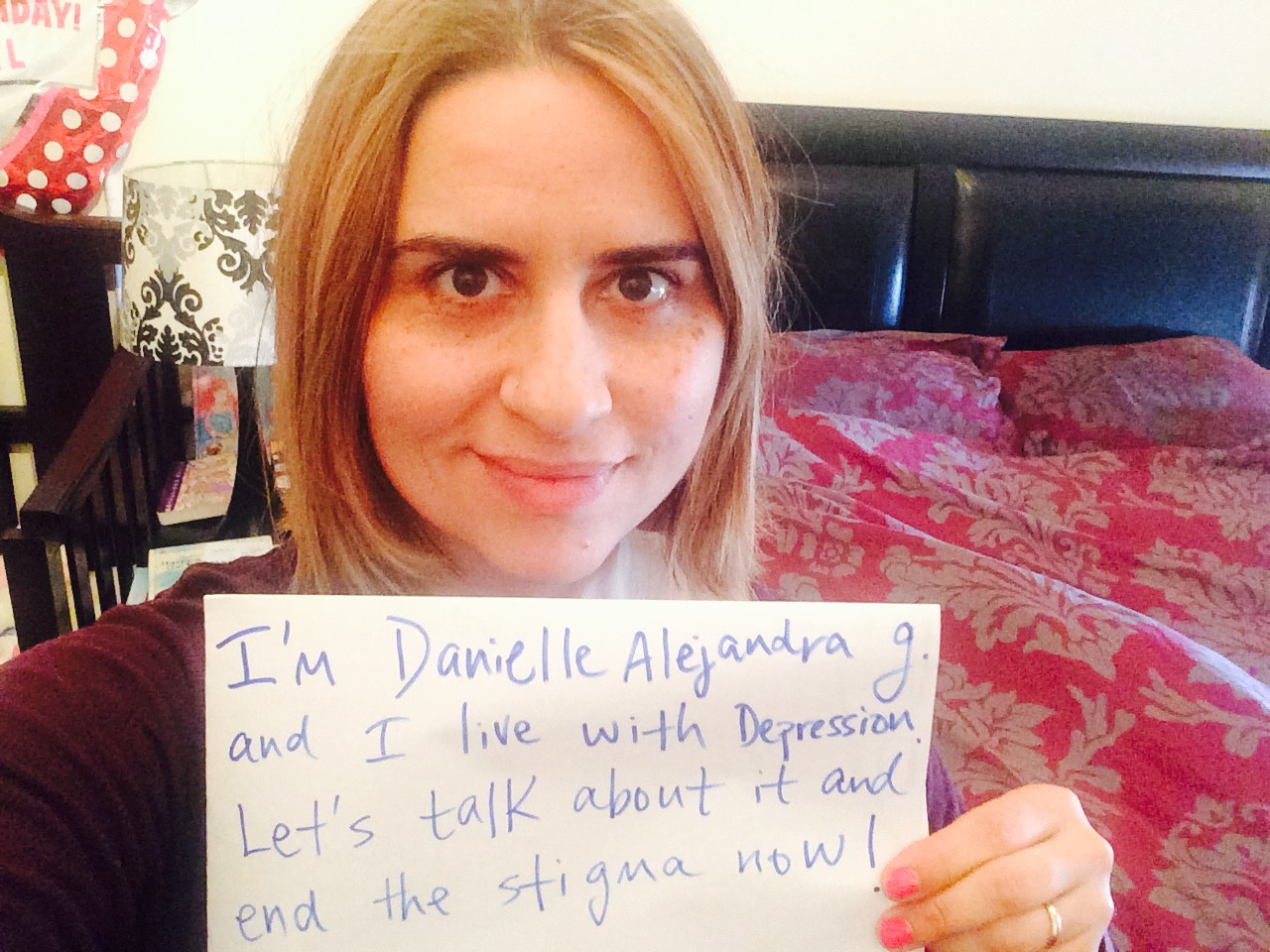 "Sign: ""I'm Danielle Alejandra G. and I live with depression. Let's talk about it and end the stigma now""  Image description: Danielle is multiracial. She has short light brown hair, hazel eyes and freckles. She is wearing a long sleeved magenta top."