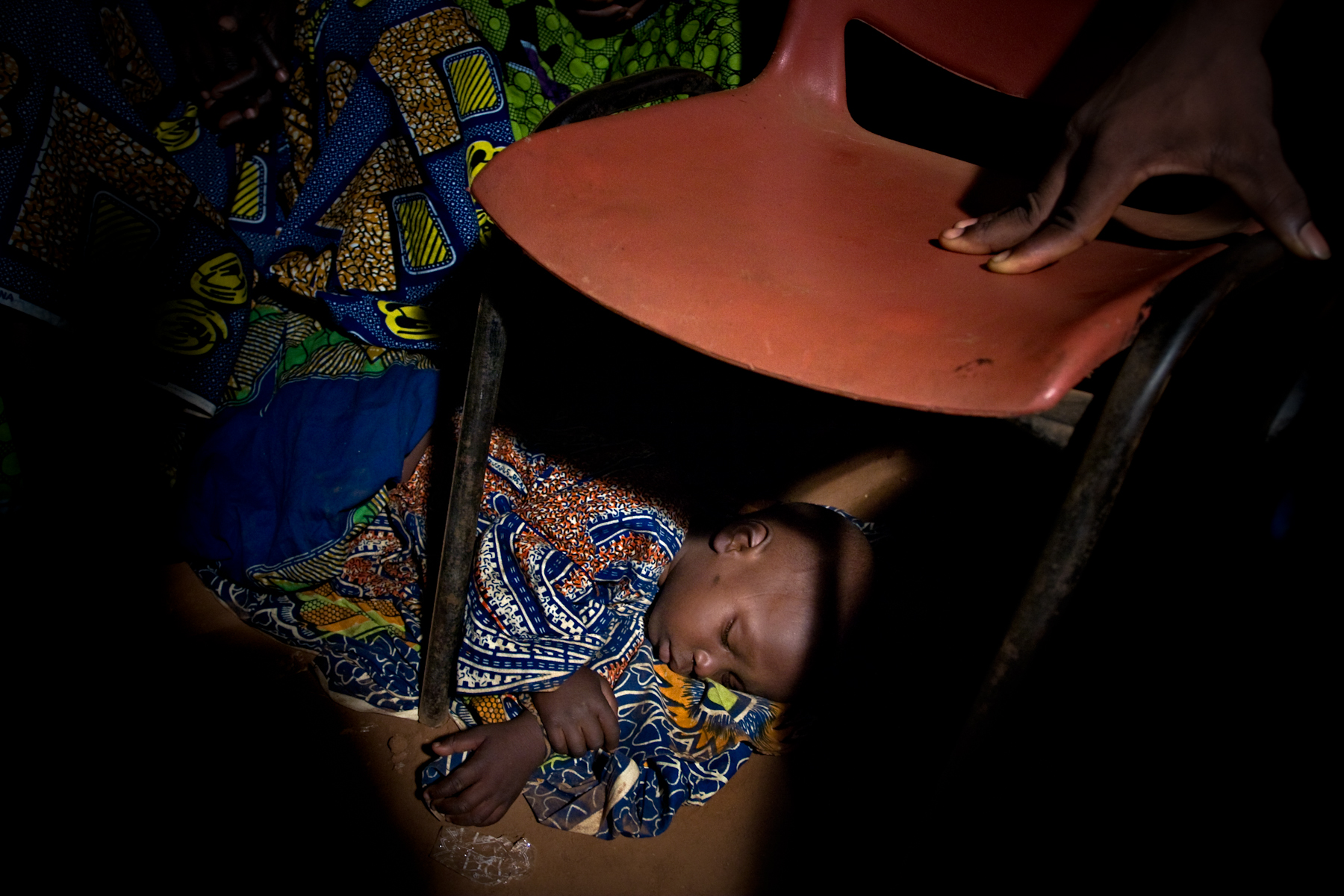 Child asleep under a chair during an all night gelede dance ceremony held as part of the extended funeral ceremonies for a local dignitary, Illara.