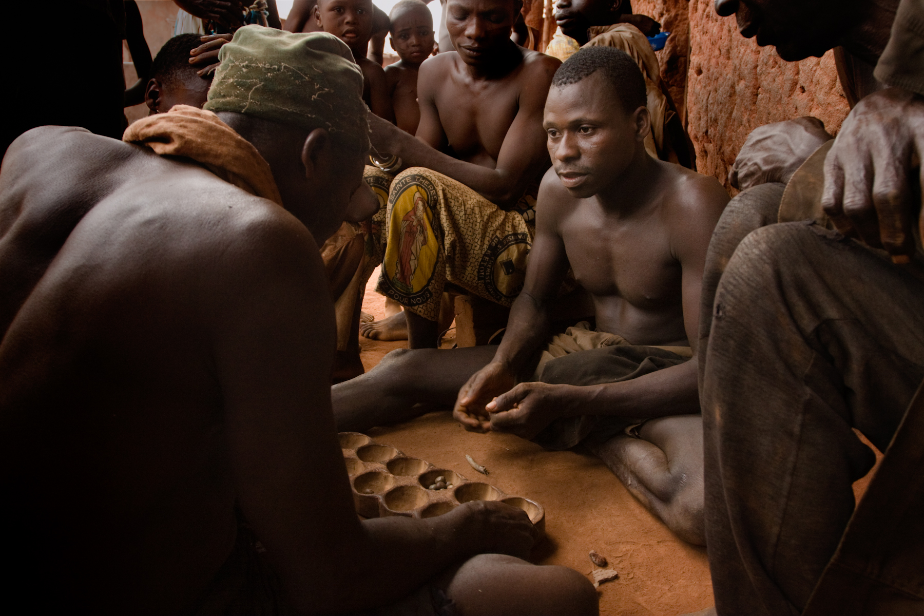 "Village men playing ""the bead game"" at the end of the day."