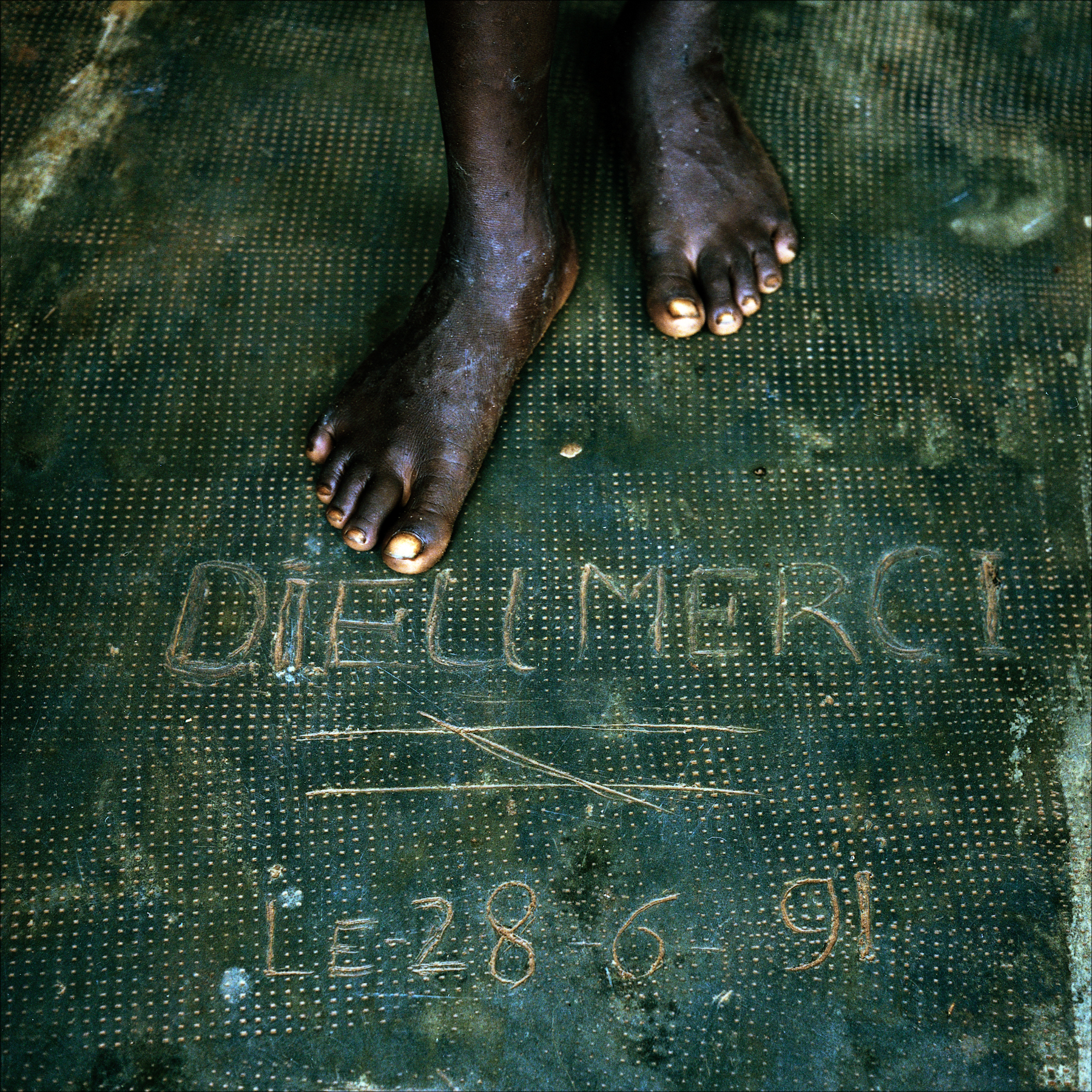 """Dieu Merci"" inscribed in the concrete threshold of a home, Ketou."