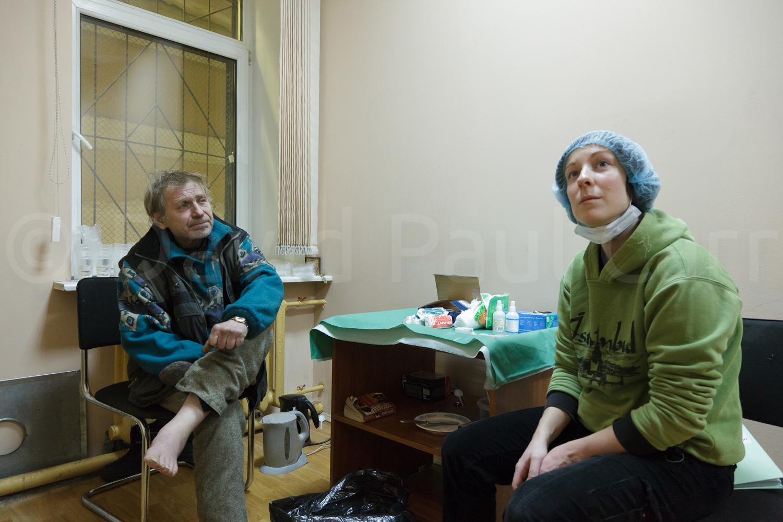 A homeless man shows his frost-bitten feet to the duty nurse.