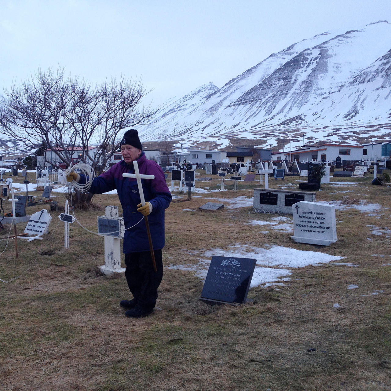 """There's been a bizarre thaw this week in Ólafsfjörður, with its seemingly bottomless mantle of snow disappearing overnight, in howling gales and warm rain. Under the ice in the town cemetery: upturned marble cherubs, candle wax, wilted bouquets. In a tradition """"stretching back as far as electricity, I'm sure,"""" says team leader Oskar, Icelanders make a donation in return for the upkeep of a luminescent cross, dug into a family grave for the month of Christmas. With snowflakes set to return after sundown, elderly members of the local Rotary Club have taken the opportunity to dig up the glowing crosses from the earth. Here, one will set you back 3,000 Krona. """"Cheapest in Iceland,"""" Oskar says proudly."""