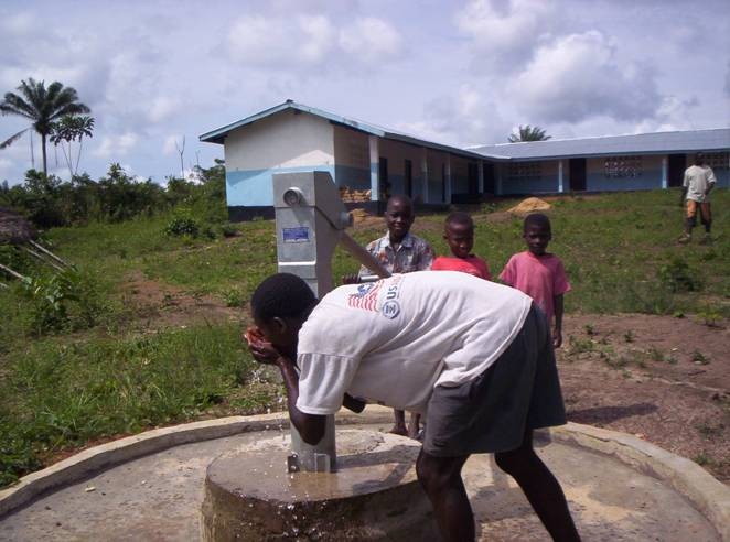 A resident of Balama uses the palms of his hands to drink clean water from the hand pump.