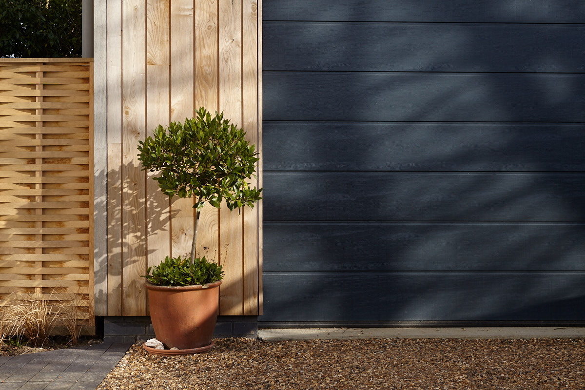 Automated Garage door against Sweet Chestnut cladding | for further information see  Sustainable House, Norton