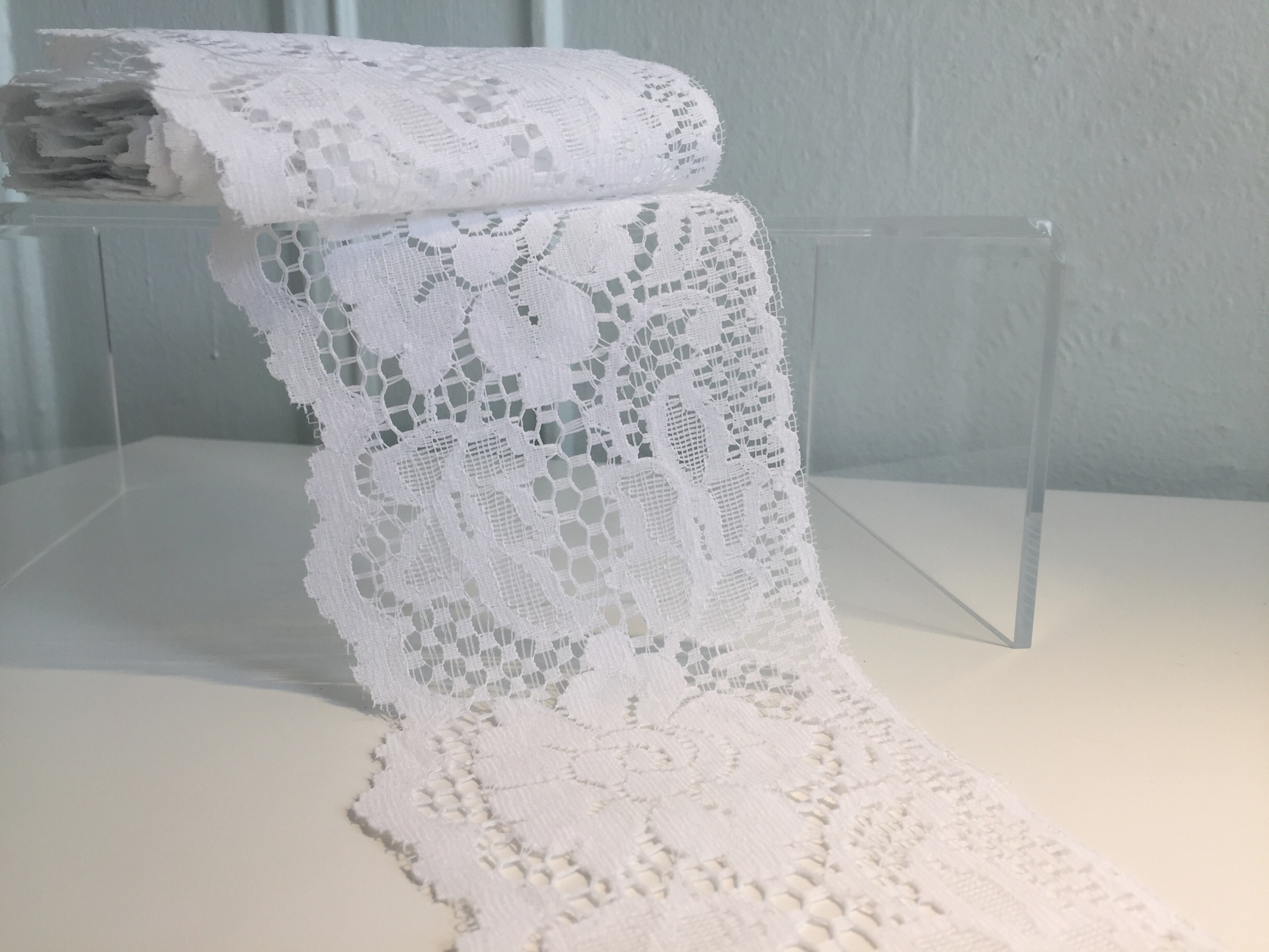 Leaver's lace: This is lace made on the Leaver's machine, developed in the early/mid 1800s from an adaptation of a net making machine and the jacquard weaving apparatus, which makes lace complete with the pattern, net, and outline, all at once. This machine-made lace incorporates some of the shading details found in finder handmade chantilly lace, without requiring a netting ground. It's generally flatter, and makes for a sturdy lace option, even if made in a more delicate design.