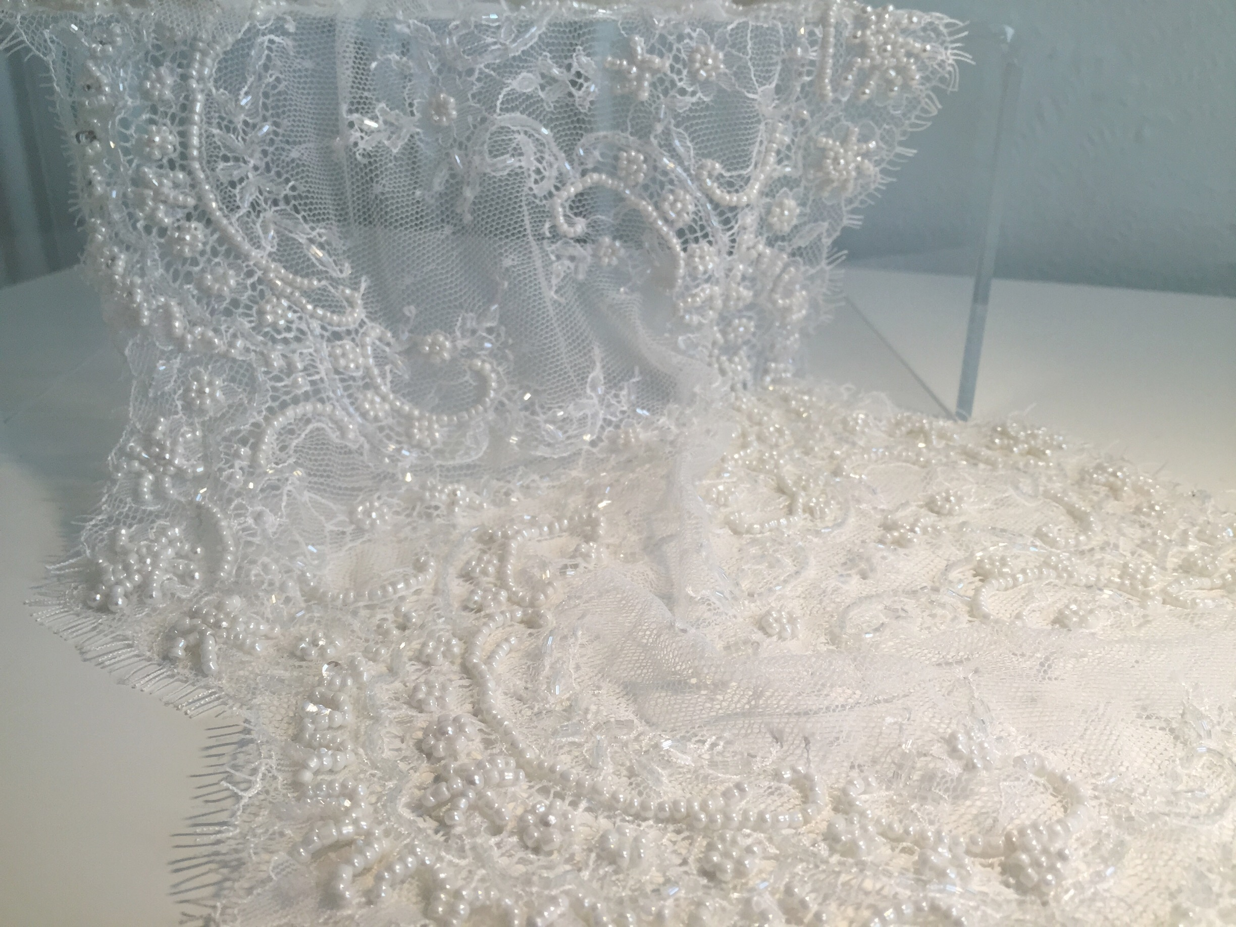 Beaded lace: A lot of chantilly and alençon laces may be beaded, particularly when it comes to bridal laces. Above is a beaded chantilly lace, with beads used to outline some of the floral motifs. This example also shows the eyelash fringe detail along the scalloped edge, which makes this a beautiful and elegant choice for a hem of train or if scallop depth allows, along a neckline and/or armhole of a bodice. When looking for beading lace, be sure to consider the additional time required to work with the fabric.