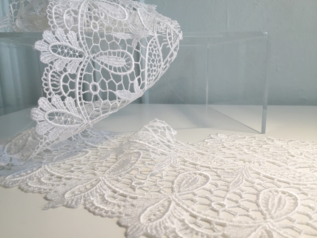 "Guipure: This heavy lace is used often in edgings and insertions, but is also used all over for a bold bridal statement. It is a denser lace than most, and is good for brides who do not like the look of netting. It is distinguishable from other laces because of the legwork or ""brides"", which are long coarse stitches, joining the design motifs, usually flowers, as opposed to being sewn onto a mesh ground. Modern guipure can be made by embroidering the motif onto a water- or chemical-soluble material, which is dissolved away after later. I particularly love it as a lace jacket or crop top over a simple dress."