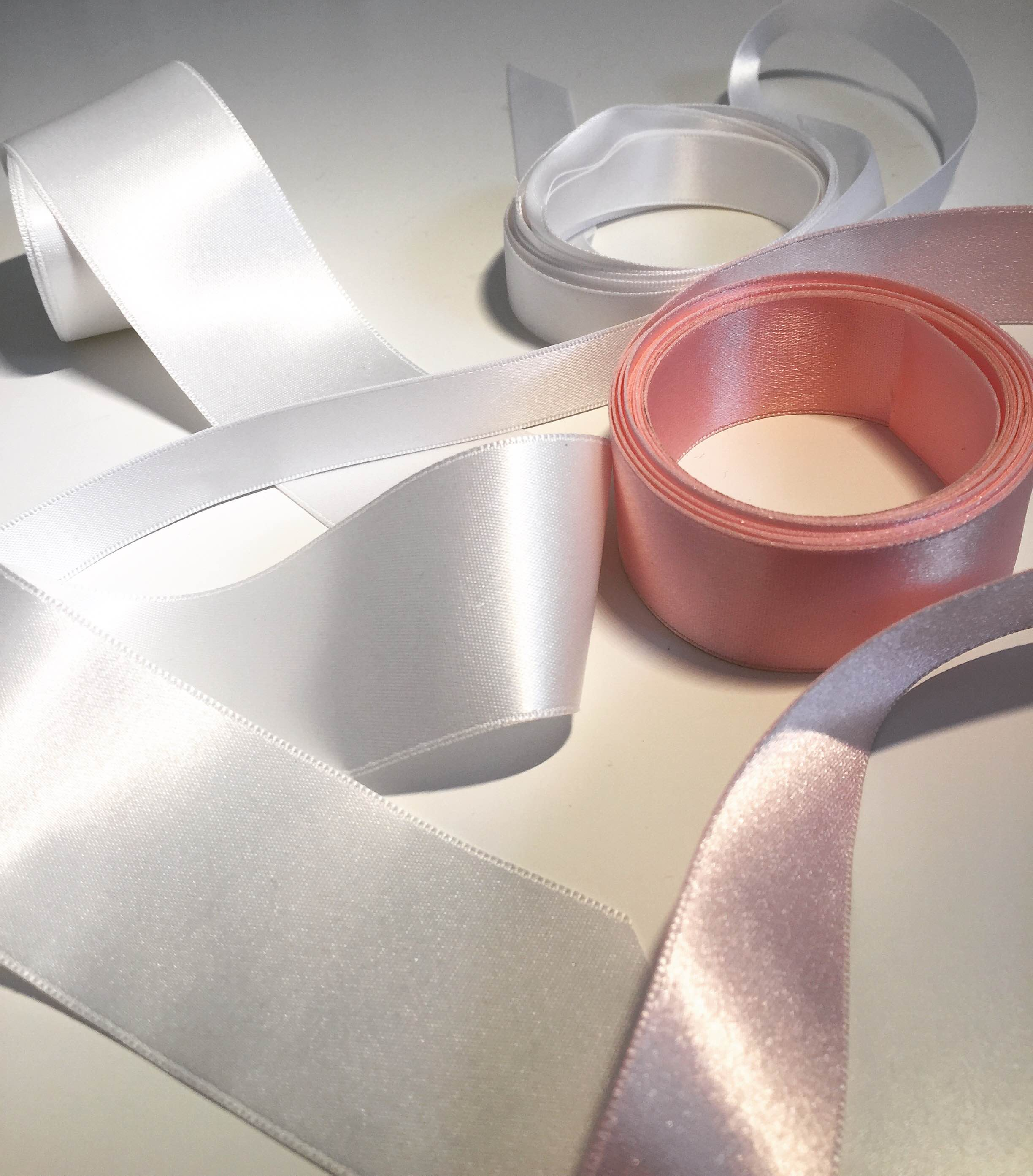 """Satin Ribbon is probably the most commonly thought of trim when it comes to bridal belts and sashes. Available in a ton of colors and variety of standard widths, usually between 1/8th"""" to 3 or 4"""", these can also come in a variety of qualities. There are thin, paper-y, stiff varieties that work better on a hat or an Easter basket, but a good bridal satin trim to search for or ask for is a double-faced polyester satin trim. Pictured here are a few of these, which are shiny on both sides, and slightly thicker than a basic satin trim. Thickness is especially important if you have a lace dress with a texture that might show through as bumps under a thinner satin. Also consider the width of the ribbon compared to the waistline on your dress and your bust size. A very thin trim may be the best way to bring waist definition on delicate dress or for a bride with a larger bust, while a more substantial dress or a bride with a smaller bust may benefit from a 2"""" wide trim. Much bigger than 2"""" is often tricky, because the shape of a waist usually curves in and out at about 1"""" above and below. Keeping an extra wide trim in place may require seams or darts to contour properly."""