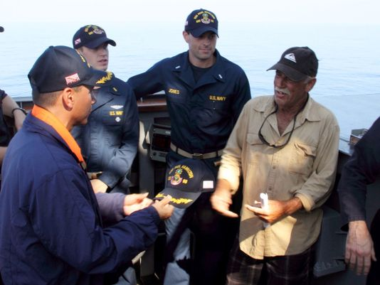 Ron Ingraham shown here with US Navy personnel on board the USS Paul Hamilton after his rescue.